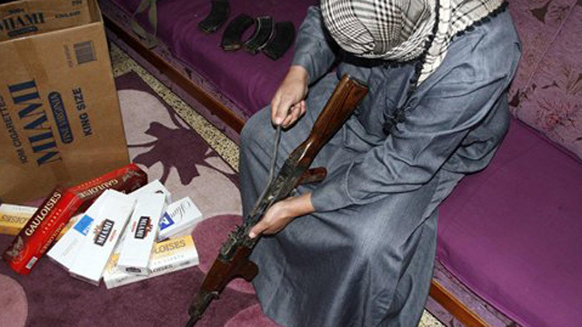 Feb. 14, 2012: Iraqi smuggler Younis al-Lehaibi, 46, dismantles an AK-47 machine-gun at his house.