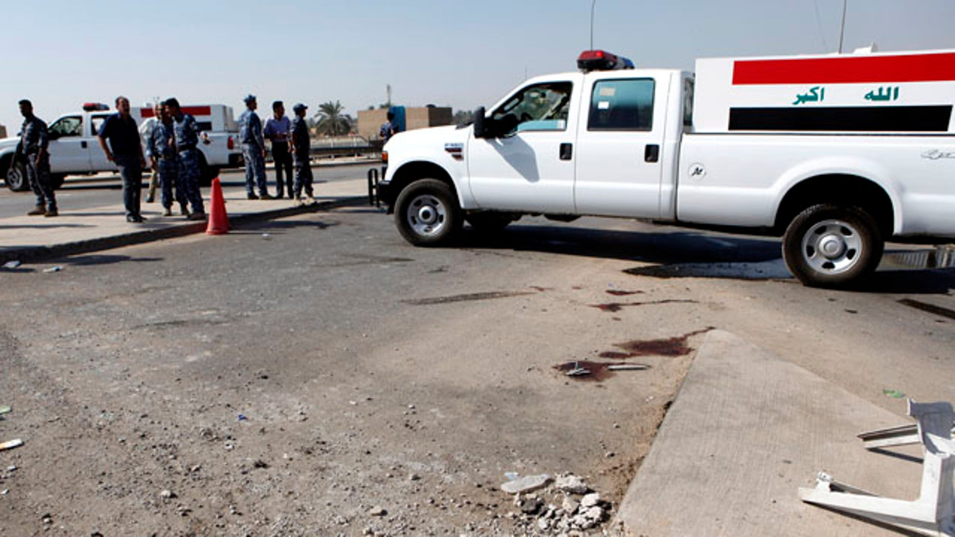 Oct. 27, 2010: Iraqi security forces inspect the scene of a roadside bomb, which exploded in northern Baghdad, Iraq, Wednesday. Iraqi police say a bombing at a checkpoint near the headquarters of a Sunni foundation in north Baghdad has killed security guards.