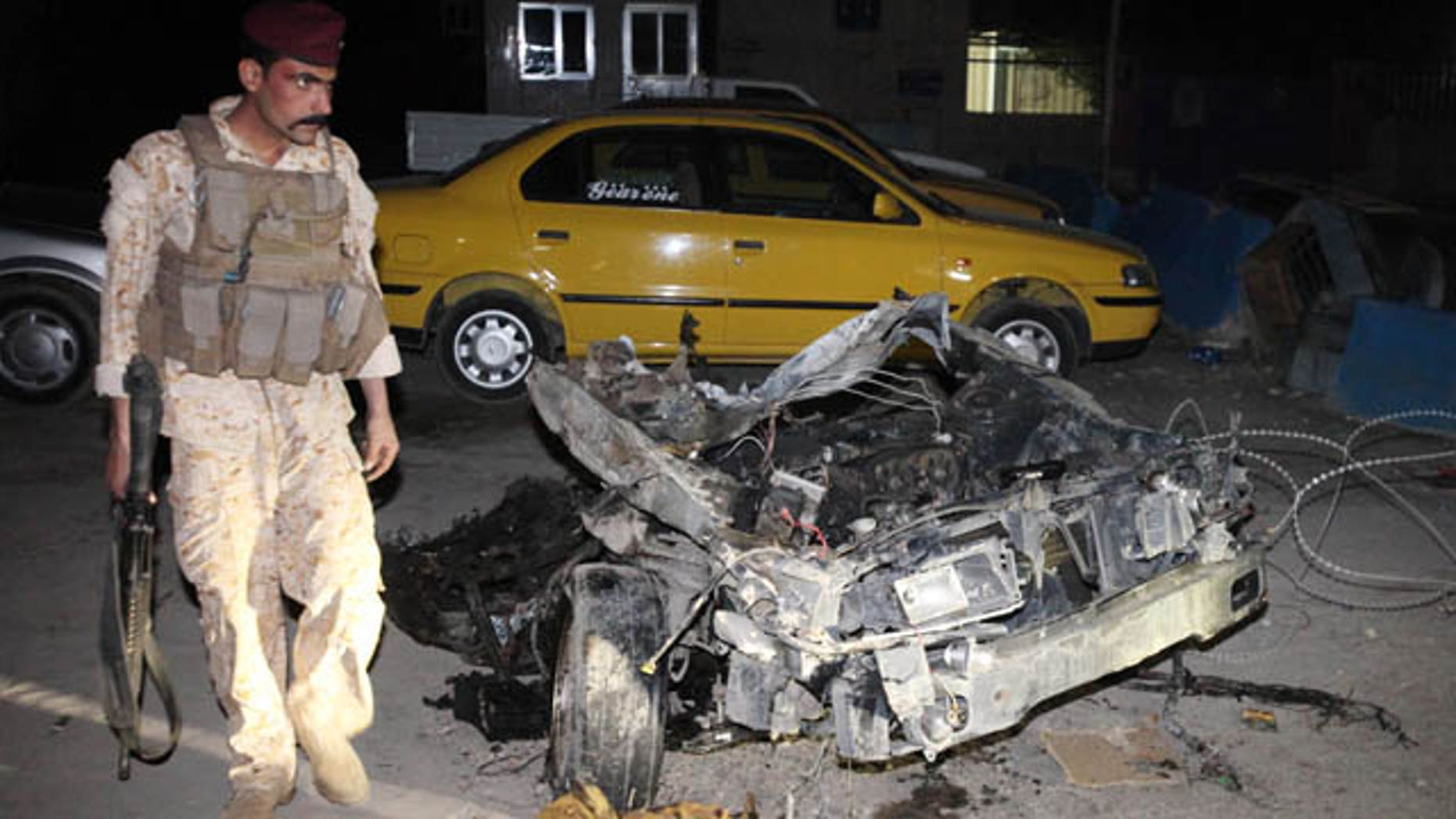 Nov. 2, 2010: An Iraqi Army soldier stands next to wreckage from a car bomb in the Shiite neighborhood of Sadr City in Baghdad, Iraq.