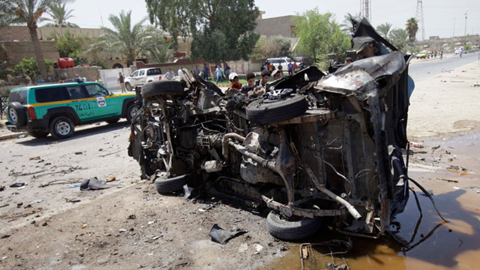 Aug. 15, 2013: Civilians inspect the aftermath of a car bomb attack in Baghdad, Iraq.