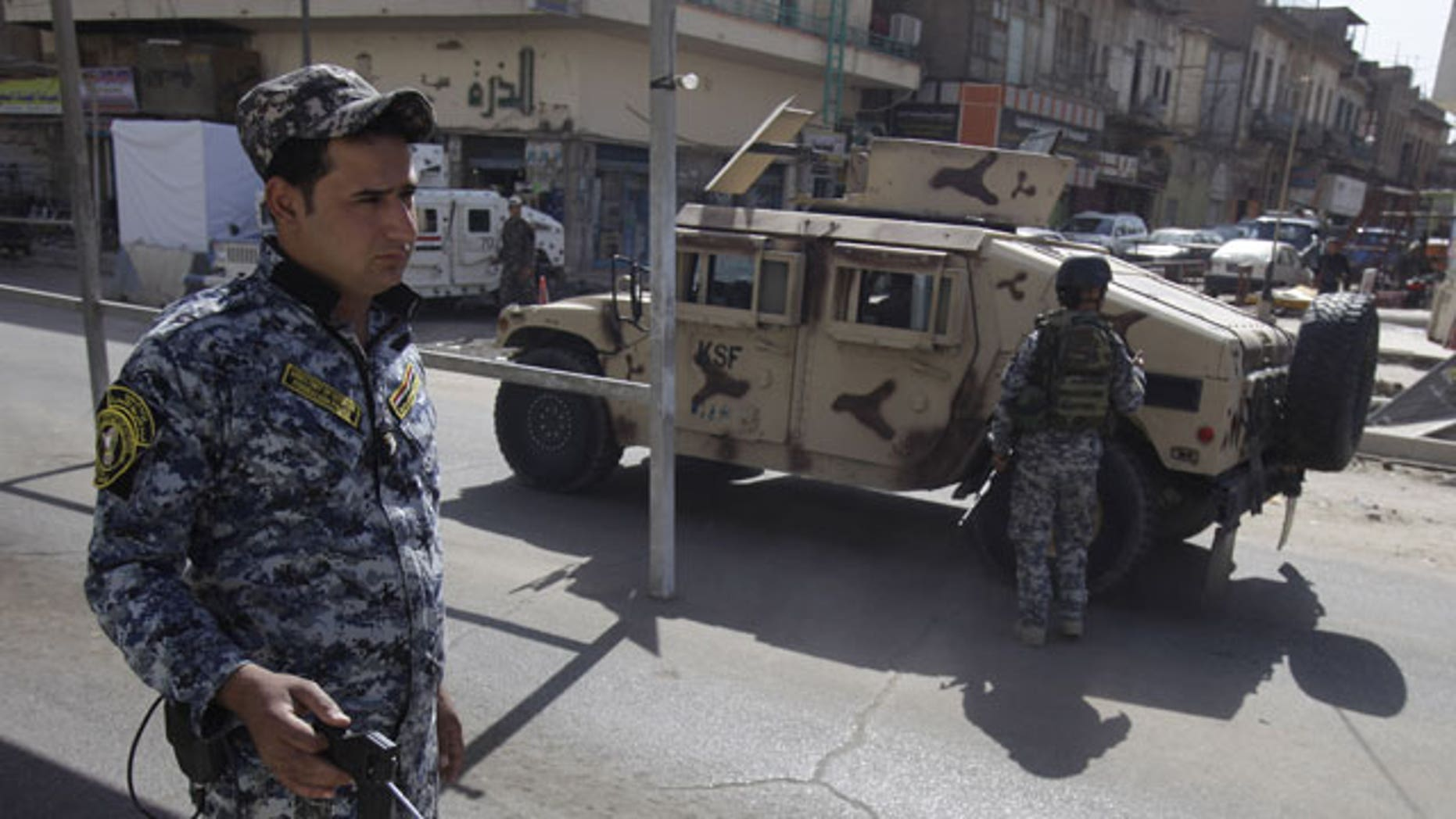 October 23: An Iraqi police officer uses a detector at a checkpoint in central Baghdad, Iraq.