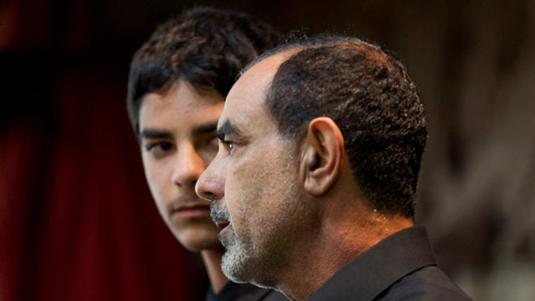 March 27, 2012: In this file photo showing Kassim Alhimidi, right, speaks alongside his son, Mohammed Alhimidi, during a memorial for his wife, Shaima Alawadi at a mosque in Lakeside, Calif.