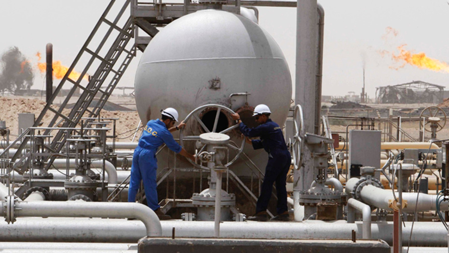 FILE 2010: Workers adjust a valve at the Rumaila oil field in Basra Province. A top Iraqi diplomat urged others to 'use the weapon of oil' against the U.S. because of its alliance with Israel.