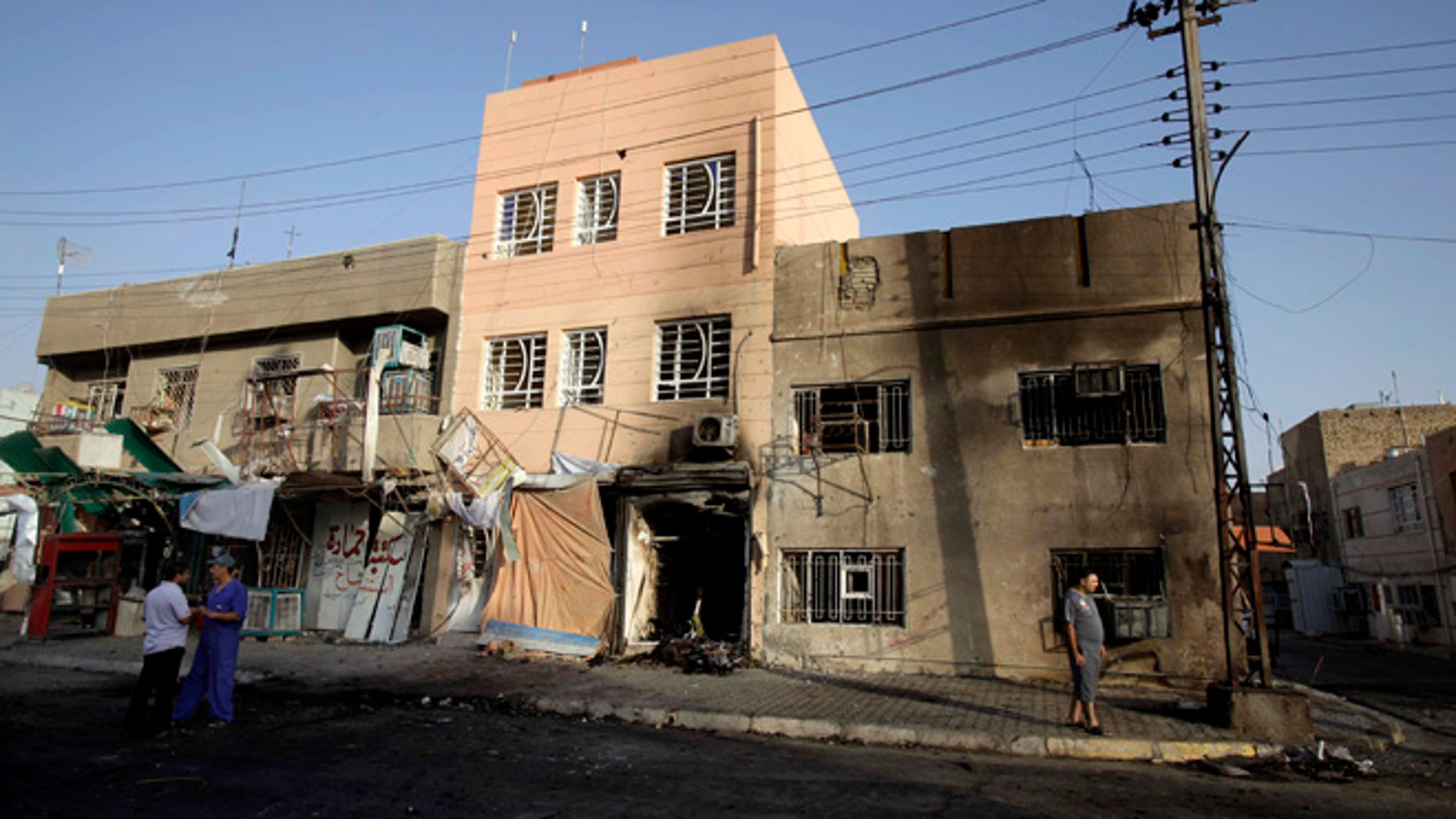 July 21, 2013: Civilians inspect the aftermath of a car bomb attack in  the neighborhood of Tobjee in Baghdad, Iraq.
