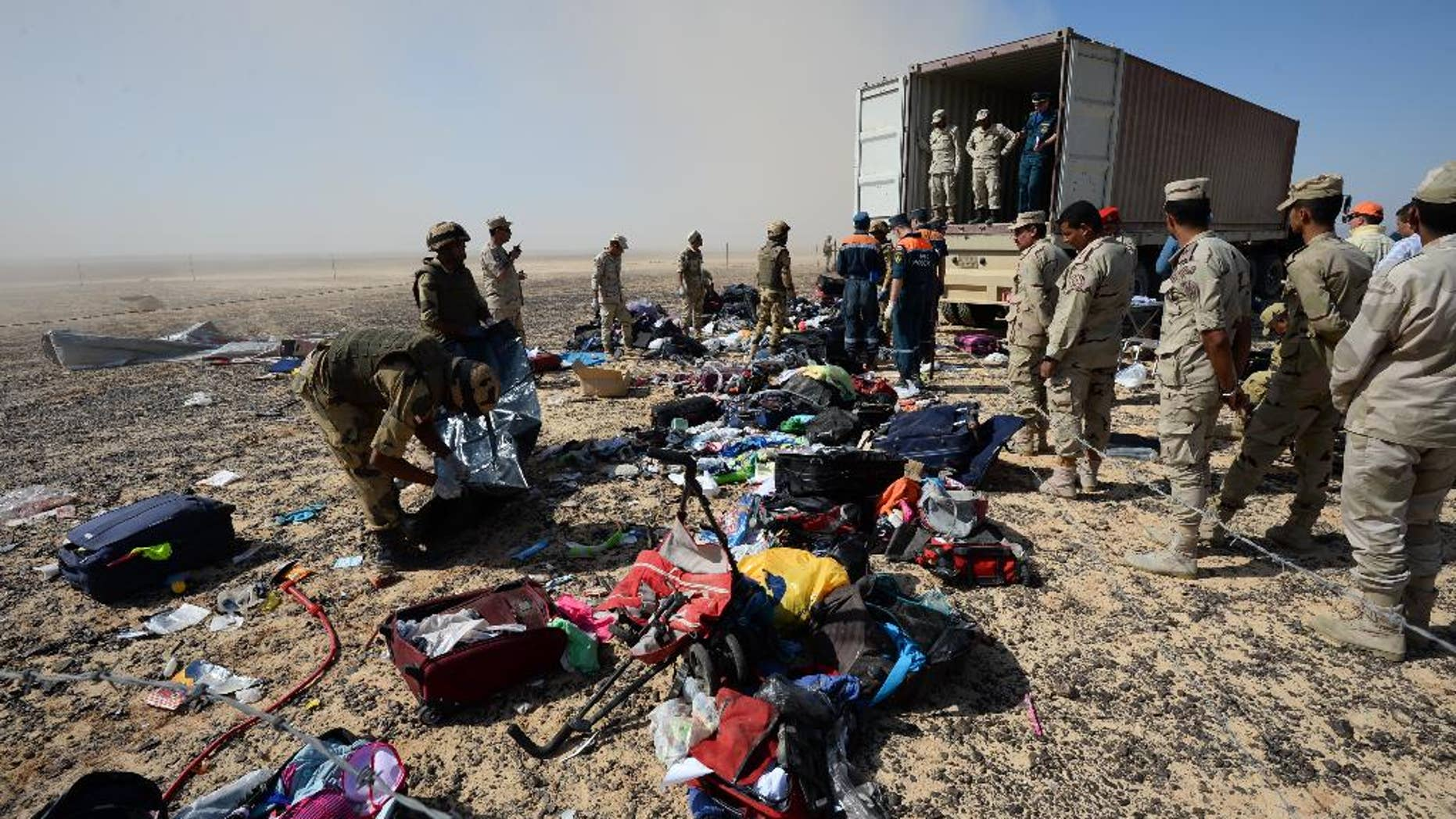 FILE - In this Monday, Nov. 2, 2015 file photo provided by the Russian Ministry for Emergency Situations, Egyptian soldiers collect personal belongings of plane crash victims at the crash site of a passenger plane bound for St. Petersburg in Russia that crashed in Hassana, Egypt's Sinai Peninsula. If an Islamic State bomb caused the Russian plane crash in Egypt, as U.S. and British officials suggest, it would mark the extremist group's largest act of transnational terrorism by far, and could  herald a new phase in its conflict with much of the world. (Russian Ministry for Emergency Situations via AP, File)