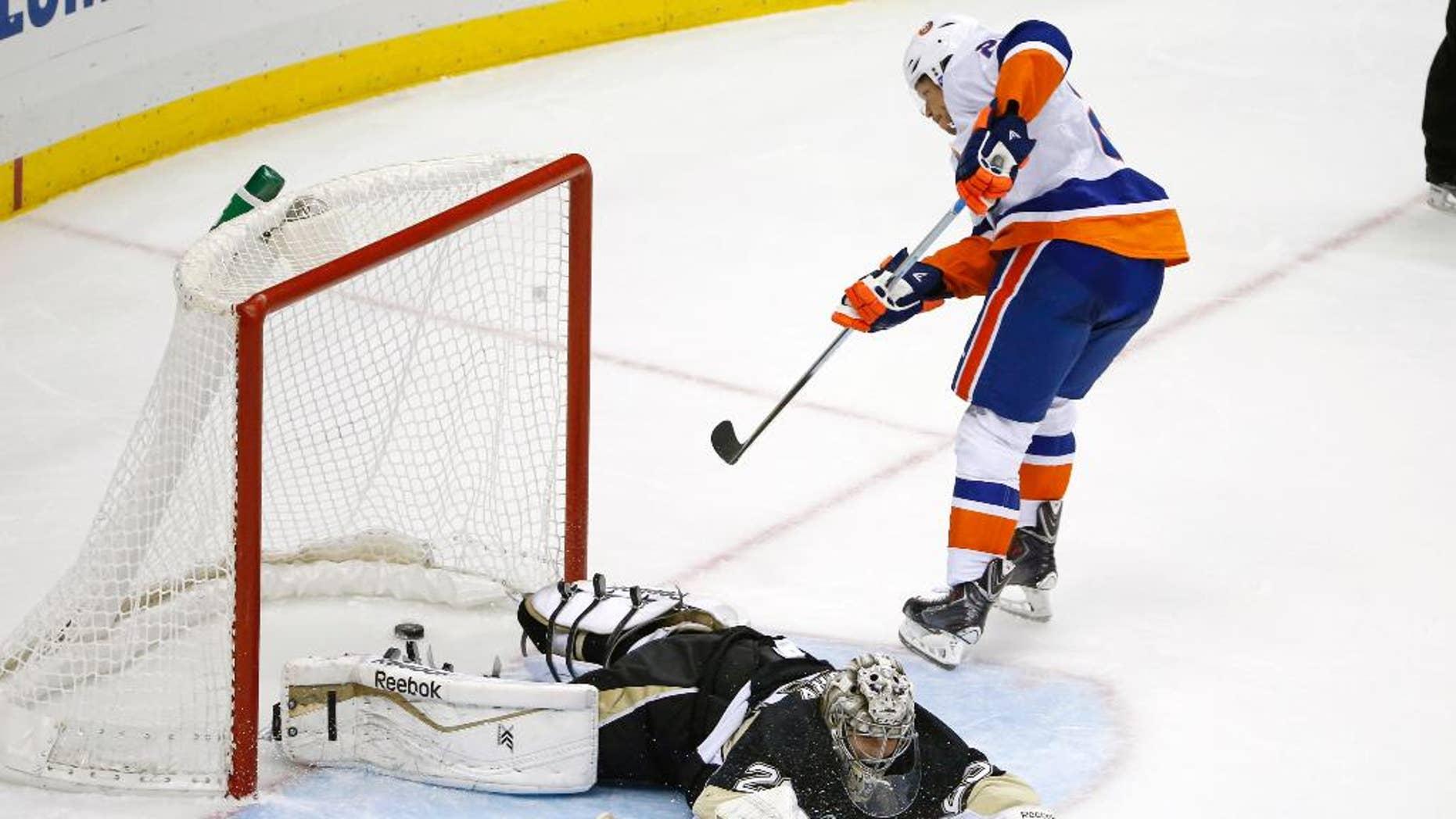 New York Islanders' Kyle Okposo (21) gets a game-winning shot past Pittsburgh Penguins goalie Marc-Andre Fleury (29) during a shootout of an NHL hockey game in Pittsburgh Friday, Nov. 21, 2014. The Islanders won 5-4. (AP Photo/Gene J. Puskar)