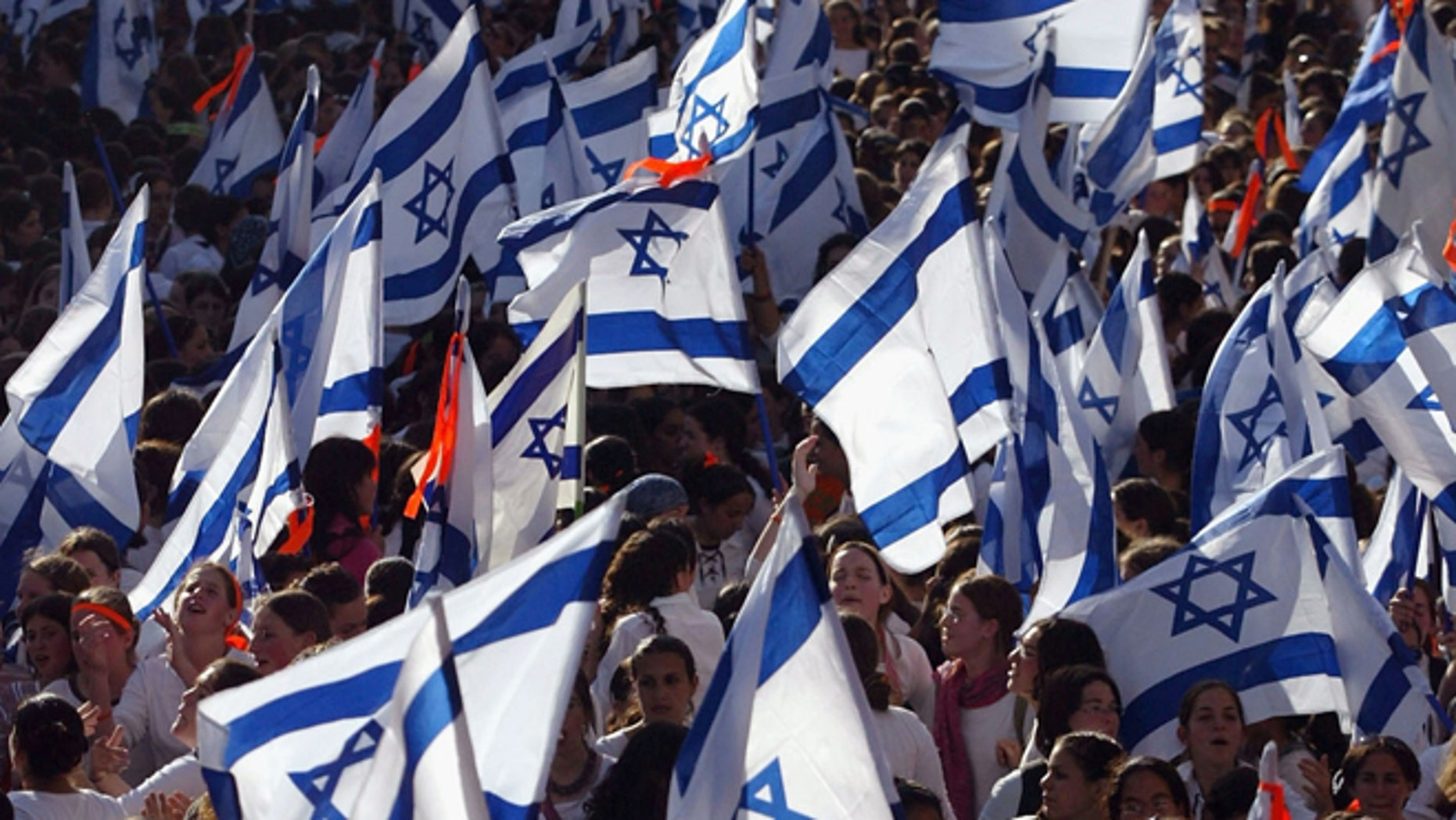 JERUSALEM, ISRAEL - JUNE 06: (ISRAEL OUT) Israeli nationalists wave the flags as they dance and march in the streets during a parade marking Jerusalem Day, June 6, 2005 in central Jerusalem, Israel. Thousands of nationalist Israelis marked Jerusalem Day, the 38th anniversary of the unification of Jerusalem under Israeli rule in 1967. (Photo by Uriel Sinai/Getty Images)