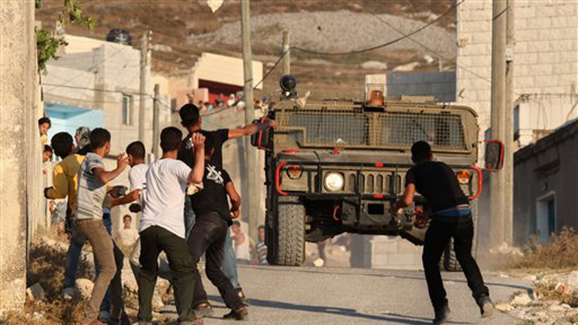 July 3, 2011: Palestinian youths hurl stones at Israeli troops during clashes over farming land between the Jewish settlement of Yitzhar and the nearby West Bank village of Asira, near Nablus.