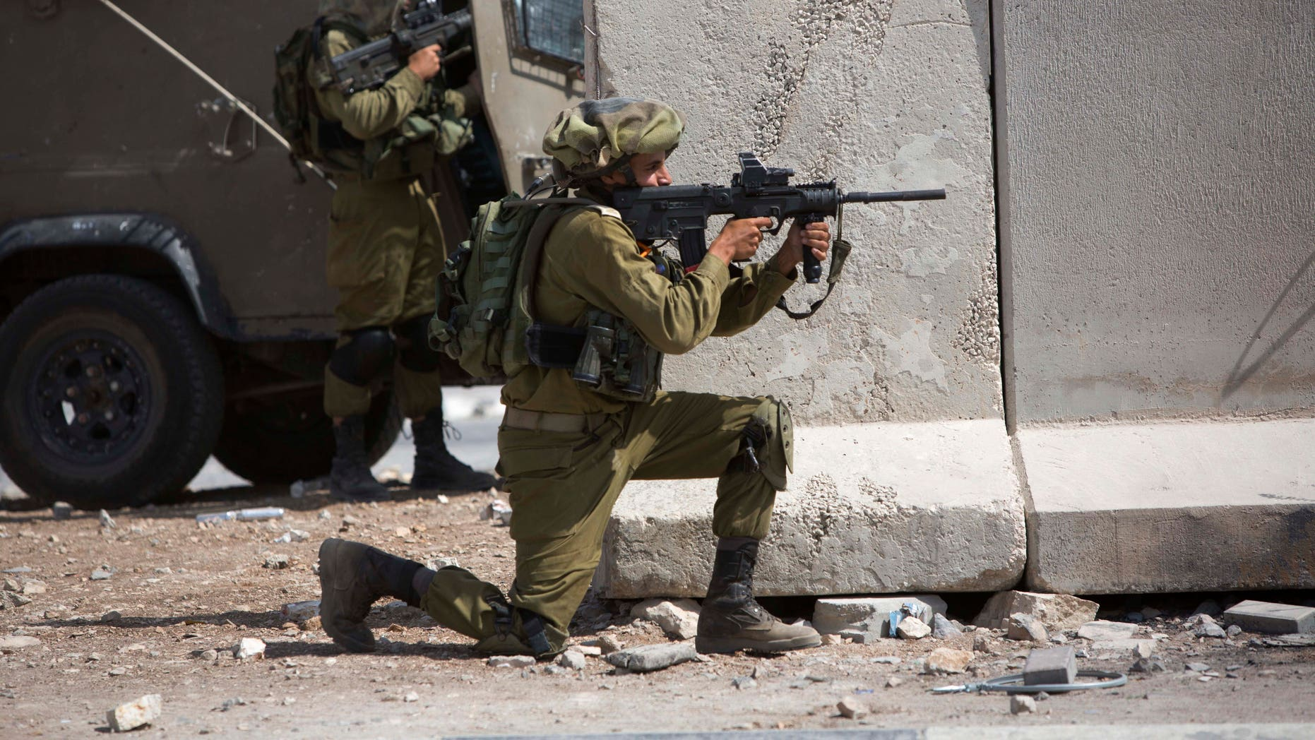 Sept. 15, 2015 - An Israeli soldier aims his weapon towards Palestinians following a demonstration at the Al-Aqsa mosque compound in Jerusalem's Old City, during clashes in the West Bank town of al-Ram. Violence between Palestinian protesters and Israeli security forces spread beyond the walls of Jerusalem's old city Friday, with at least  8 Palestinians shot in clashes in the West Bank and Israeli policemen injured by firebombs.