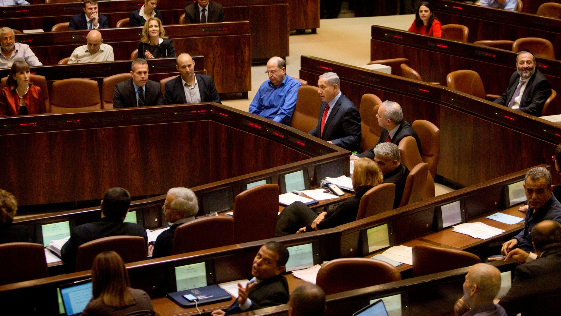 Dec. 3, 2014 - Israeli Prime Minister Benjamin Netanyahu, center, sits during a vote at the Knesset, Israel's parliament in Jerusalem. Israeli lawmakers overwhelmingly voted to dissolve parliament Monday, officially kicking off the country's election campaign.