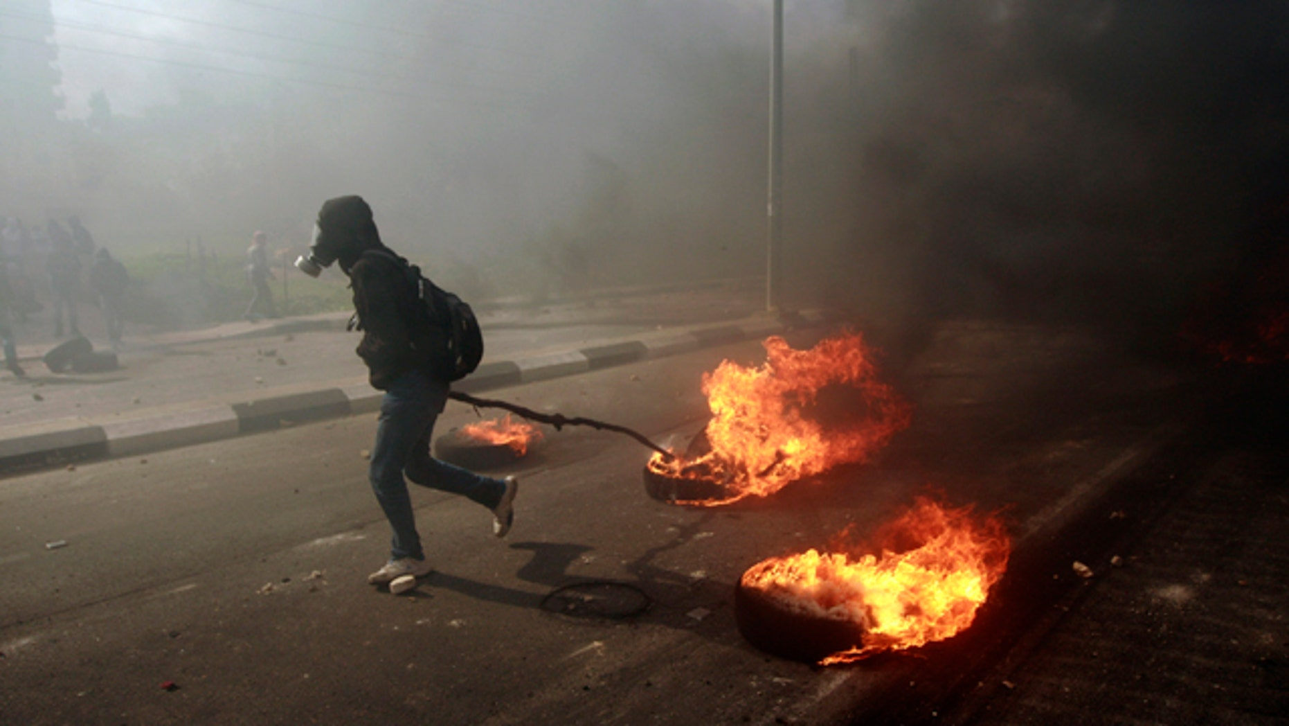 Feb. 25, 2013: A man burns tires during a protest to support Palestinian prisoners, outside Ofer, an Israeli military prison, near the West Bank city of Ramallah.
