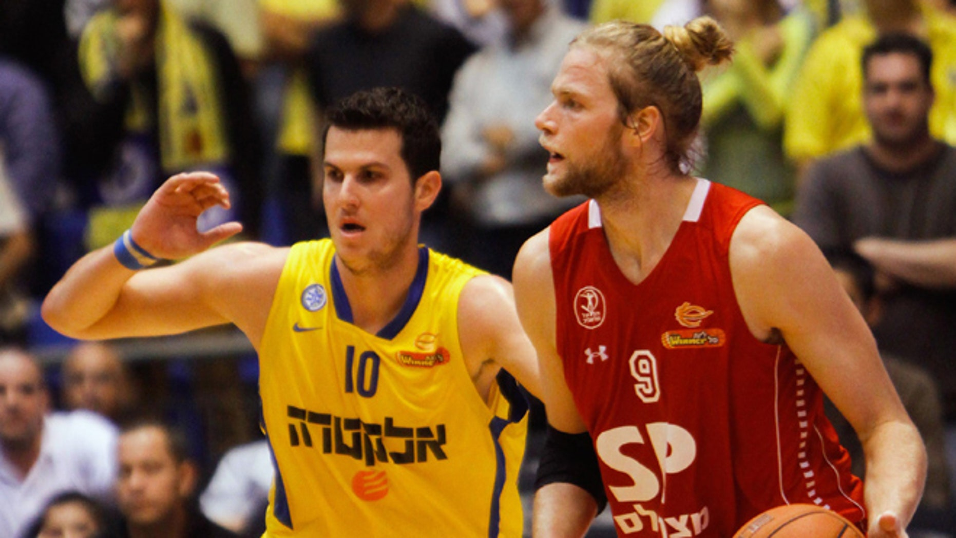 Dec. 2, 2012: In this photo, Maccabi Tel Aviv basketball club captain Guy Pnini, left, and Hapoel Tel Aviv player Jonathan Skjöldebrand, play during a match between the clubs in Tel Aviv.