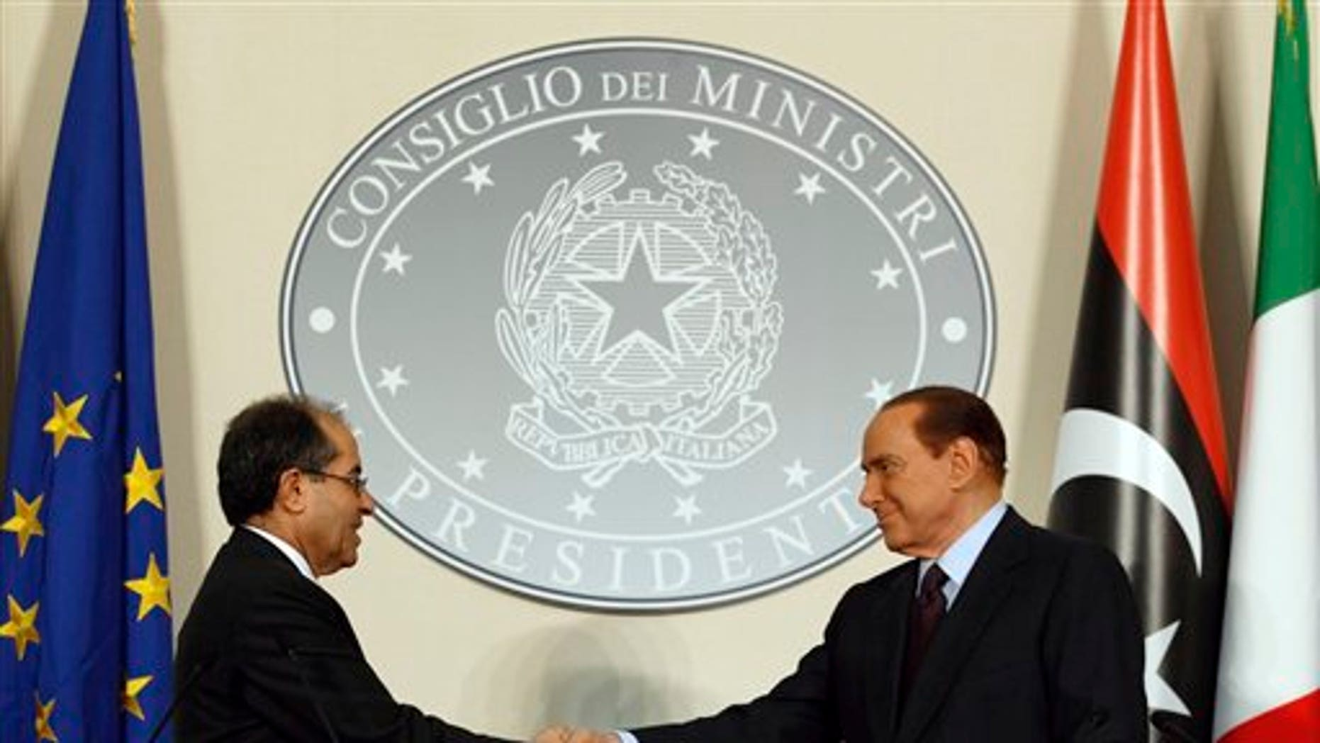 August 25: Italian premier Silvio Berlusconi, right, shakes hands with Mahmoud Jibril, deputy chairman of the Libyan National Transitional Council, during their meeting at the prefecture building in Milan, Italy.