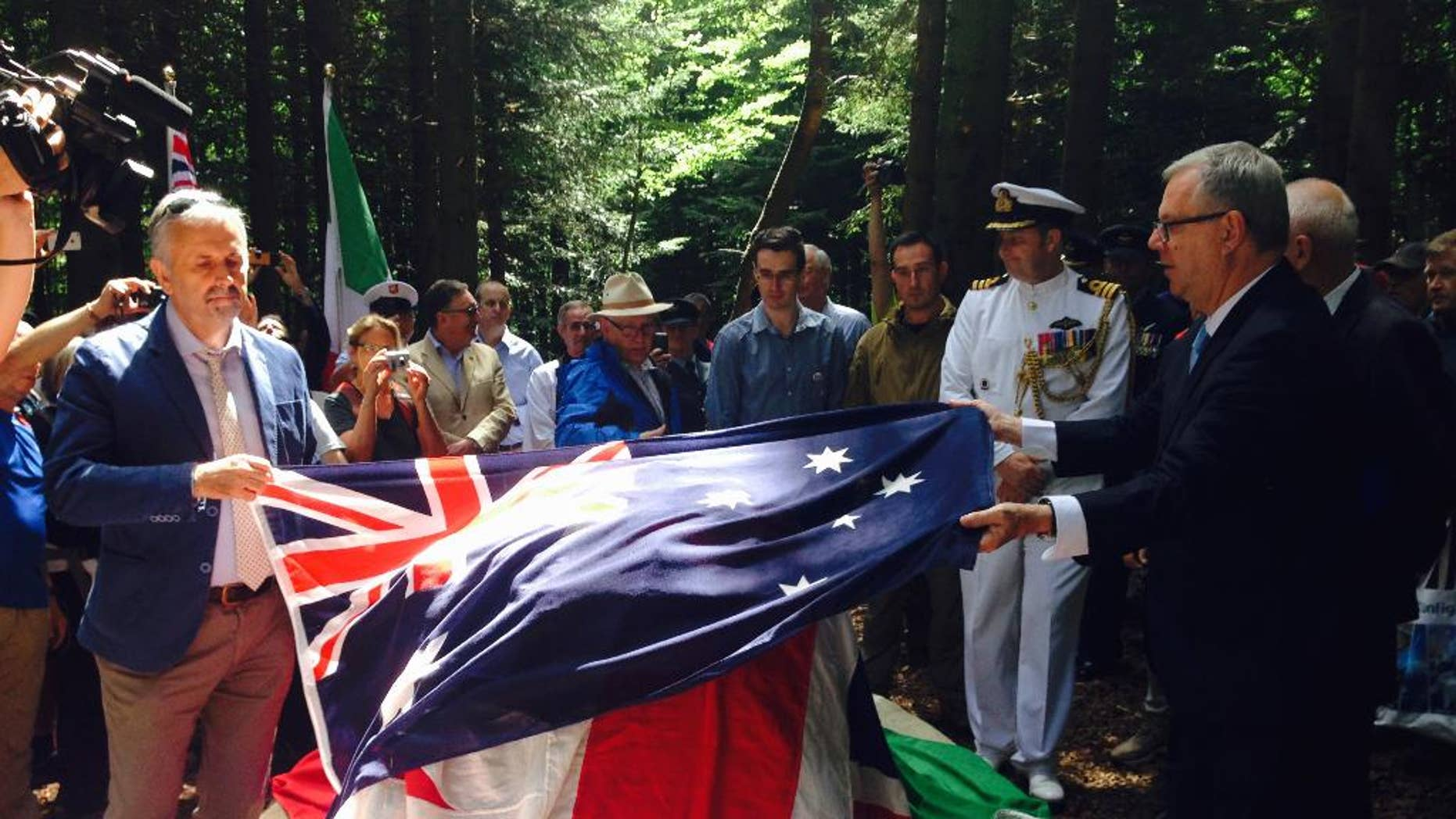 Australian ambassador to Italy, Mike Rann, right, lays the Australian flag on the occasion of the unveiling of a memorial dedicated to the Australian aviator Bert Hinkler in Castel San Niccolò near Arezzo, Tuscany, central Italy, Sunday, Aug. 2, 2015. The pilot died in an accident 1933 and for decades it has been unclear where he exactly fell, but thanks to discovery of new photos and the effort of local researchers it was possible to find the crash point on the Pratomagno mountain, in Arezzo province. (AP Photo/Paolo Santalucia)