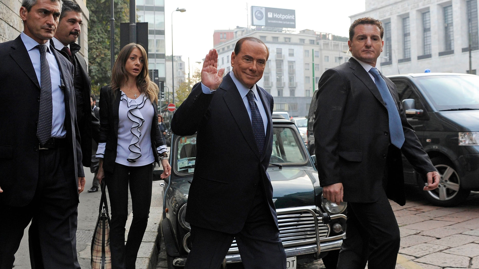 Former Italian Premier Silvio Berlusconi salutes as he arrives for a court hearing in Milan, Italy, Friday, Oct. 19, 2012. Berlusconi has denied in court having had sex with an underage Moroccan girl, or ever paying for sex with any guest at his villa near Milan, and insisted that no gathering of a sexual nature took place at his residence. Berlusconi made the remarks during a rare appearance at his ongoing trial on charges of having paid for sex with teenager Karima el-Mahroug and using his influence to cover it up. (AP Photo/Gian Mattia D'Alberto, Lapresse) ITALY OUT