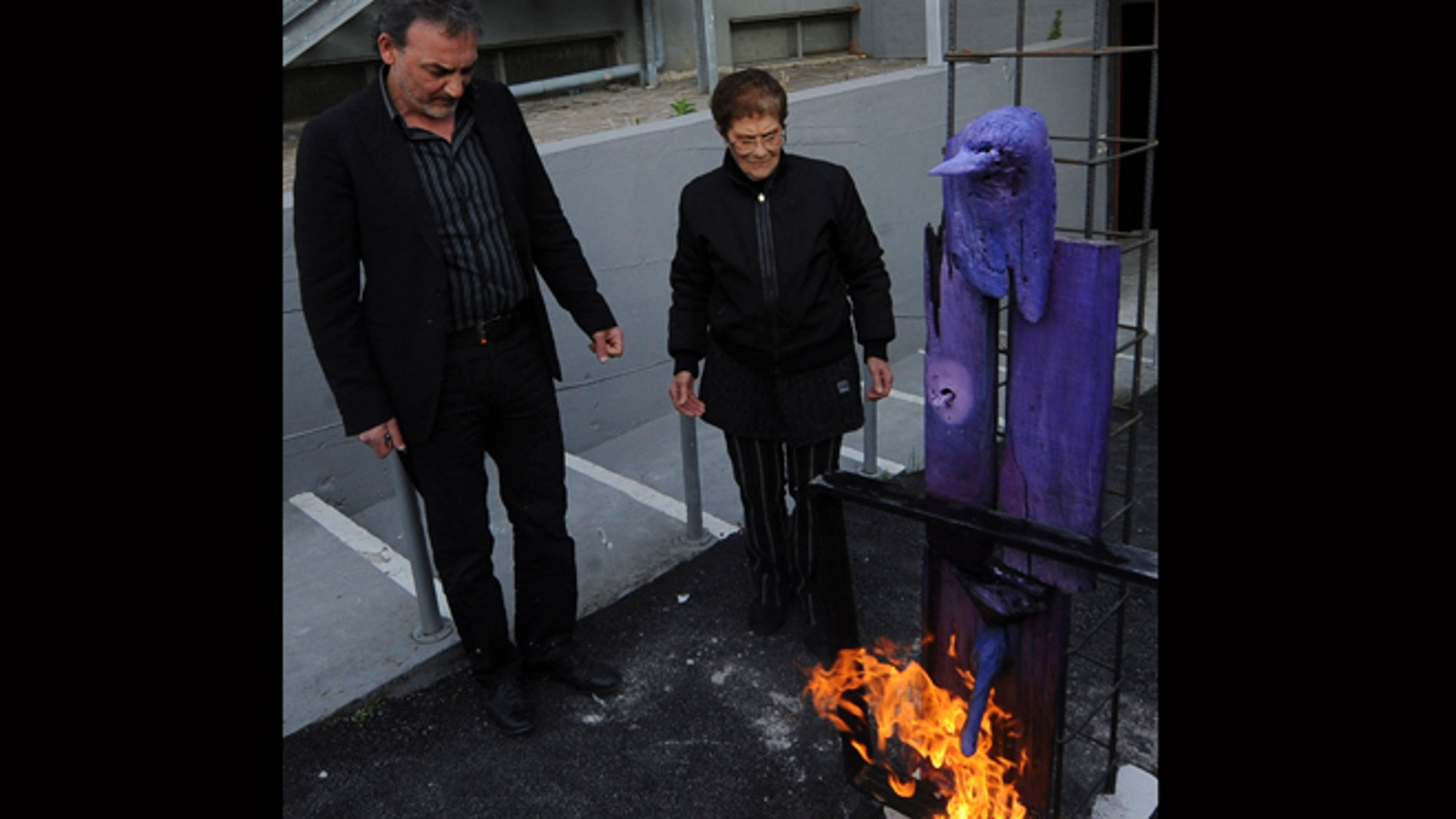 April 18, 2012: Antonio Manfredi, left, director of the Casoria Contemporary Art Museum, and Italian artist Rosaria Matarese burn one of Matarese's creations in front of the museum, near Naples.