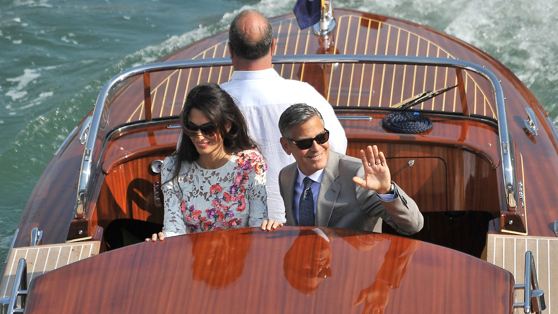 George Clooney and his wife Amal Alamuddin, cruise the Grand Canal after leaving the Aman luxury Hotel in Venice, Italy, Sunday, Sept. 28, 2014. George Clooney married human rights lawyer Amal Alamuddin Saturday, the actor's representative said, out of sight of pursuing paparazzi and adoring crowds. (AP Photo/Luigi Costantini)