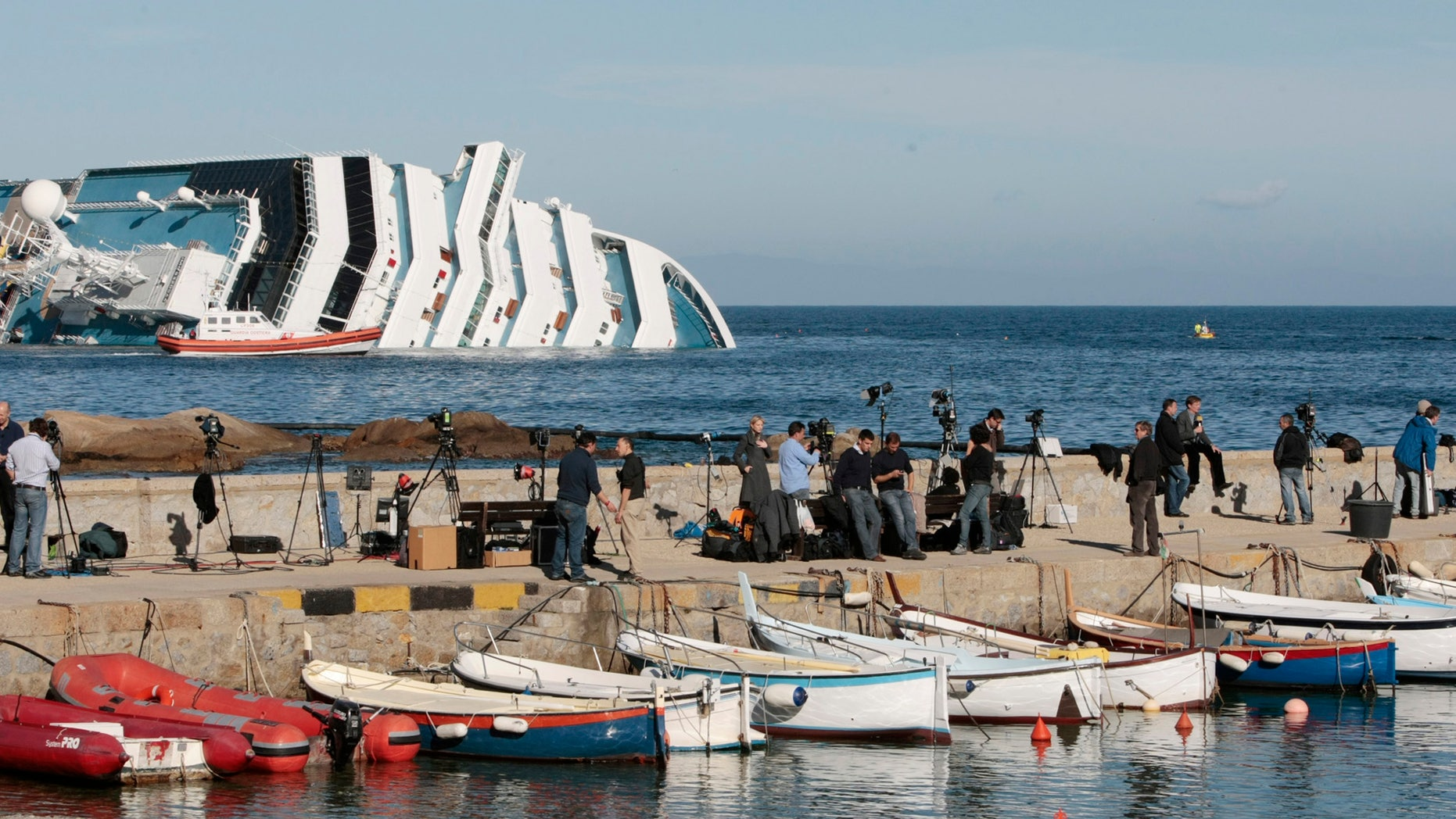 Jan. 20, 2012: Media crews stand on the harbor wall facing the Costa Concordia cruise liner off the tiny Tuscan island of Giglio, Italy.