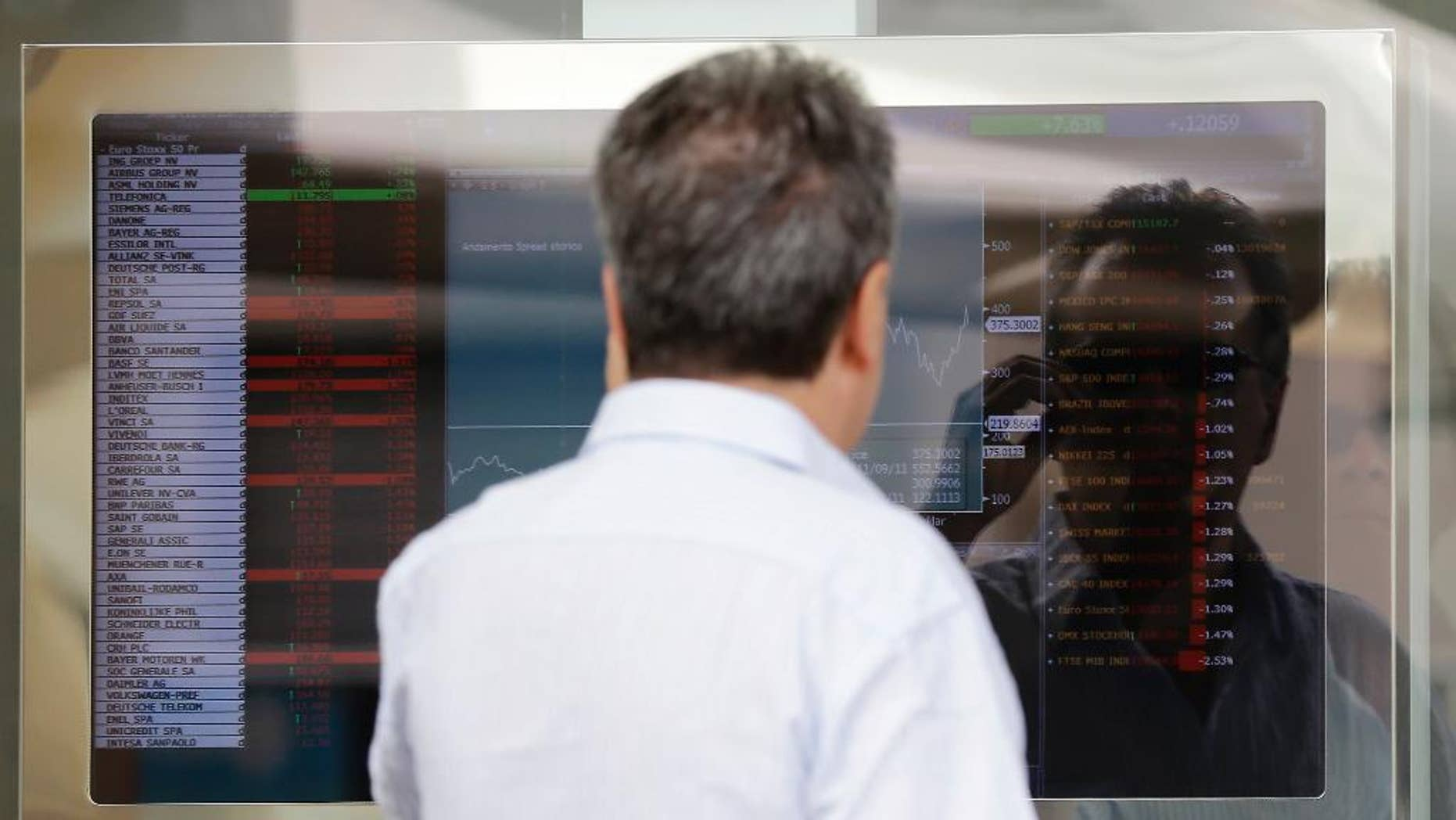 A man watches a stock exchange board monitor outside a bank, in Milan, Italy, Wednesday, Aug. 6, 2014. Pressure is building on Premier Matteo Renzi to push through reforms to restart Italy's economy after the national statistics agency reported that the economy had slipped back into recession. The ISTAT statistic agency on Wednesday estimated that the Italian economy contracted by 0.2 percent in the second quarter, the second straight quarter of decline. Analyst surveys had forecast slight growth. (AP Photo/Antonio Calanni)