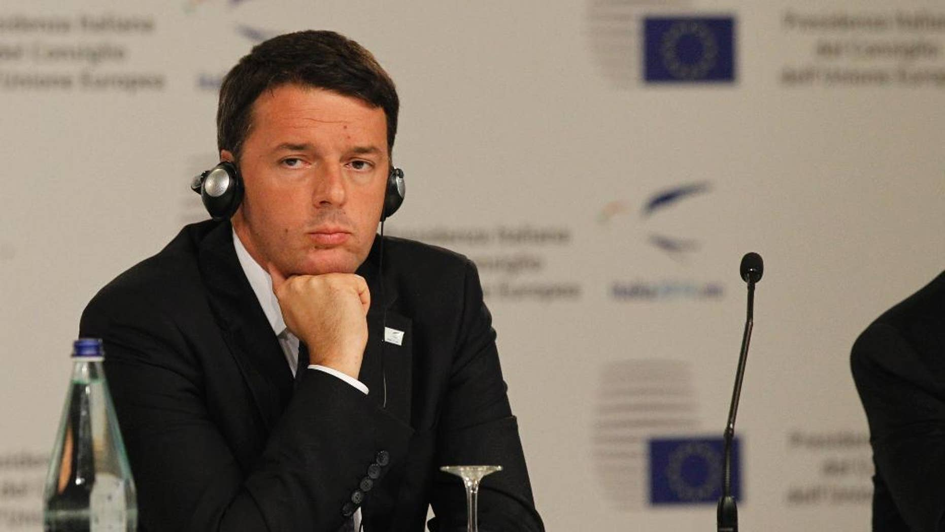 Italian Premier Matteo Renzi listens during a press conference at the EU jobs summit in Milan, Italy, Wednesday, Oct. 8, 2014. European leaders have debated ways to find work for the continent's 25 million unemployed at a summit Wednesday, as popular frustration grows at authorities' failure to return the continent's economy to health. Several thousand union activists protested outside the venue, demanding a stop to government spending austerity policies and calling for reforms to encourage investment. (AP Photo/Felice Calabro')
