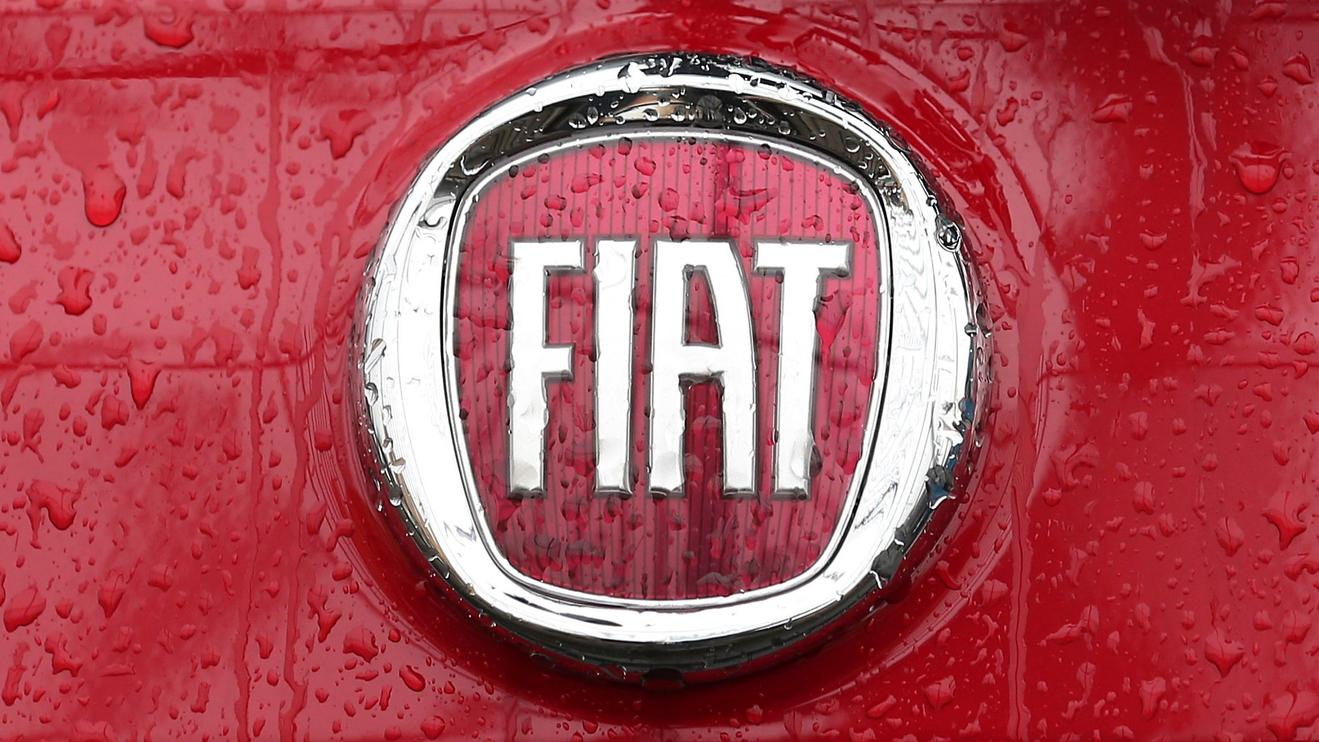 Rain falls on a Fiat logo pictured on a car  in Milan, Italy, Thursday, Jan. 2, 2014.  Italian automaker Fiat SpA announced that it reached an agreement to acquire the remaining shares of Chrysler for $3.65 billion in payments to a union-controlled trust fund. Fiat already owns 58.5 percent of Chrysler's shares, with the remaining 41.5 percent held by a United Auto Workers union trust fund that pays health care bills for retirees.( AP Photo/Antonio Calanni)