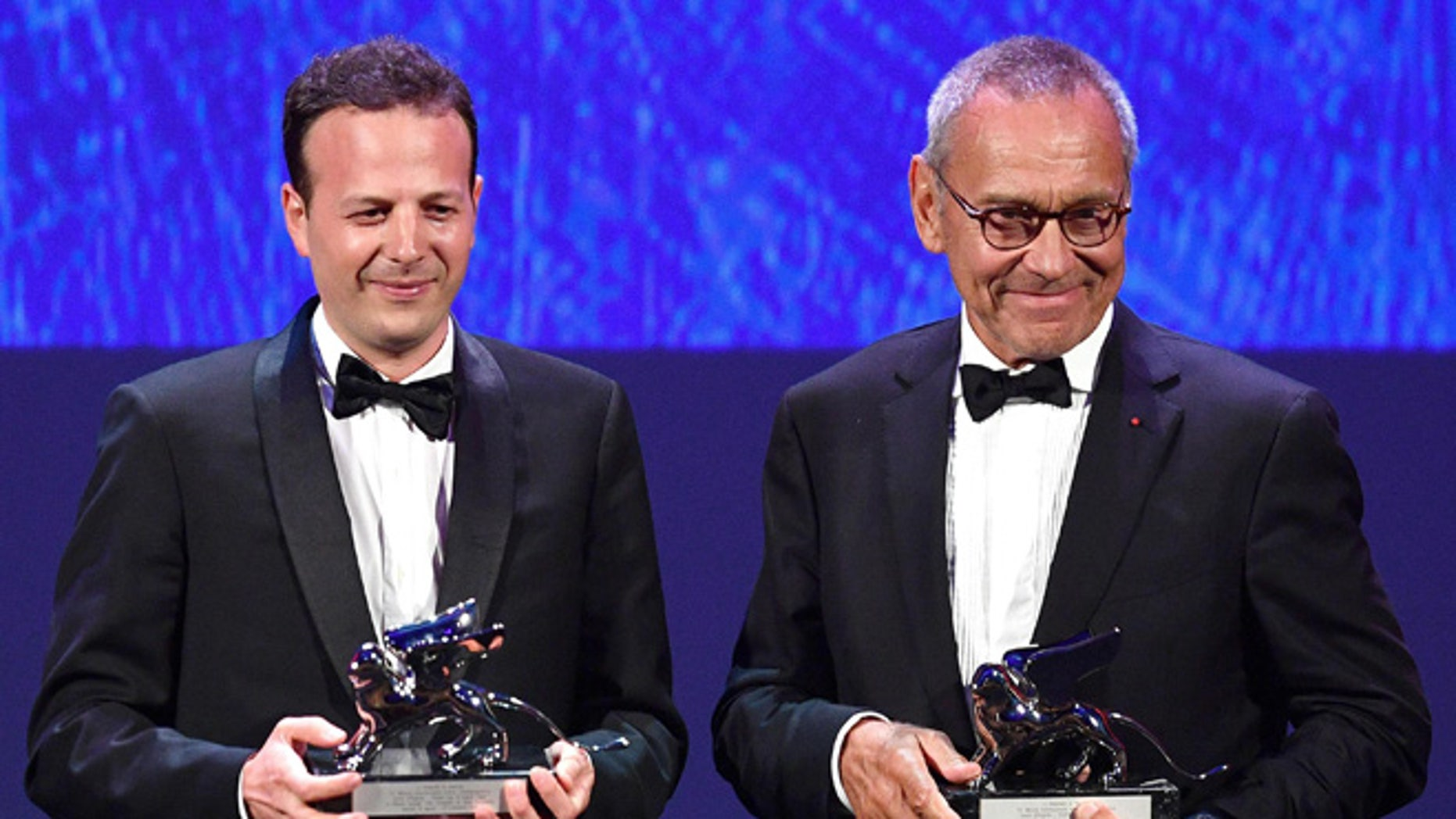 """Mexican film director, producer and screenwrite Amat Escalante, left, holds the Silver Lion award for his movie """"La Region Salvaje"""" (The Untamed) flanked by Russian director Andrei Konchalovsky, holding the Silver Lion award for his movie """"Paradise"""" during the awards ceremony of the 73rd Venice International Film Festival, in Venice, Italy, Saturday, Sept. 10, 2016. (Ettore Ferrari/ANSA via AP)"""