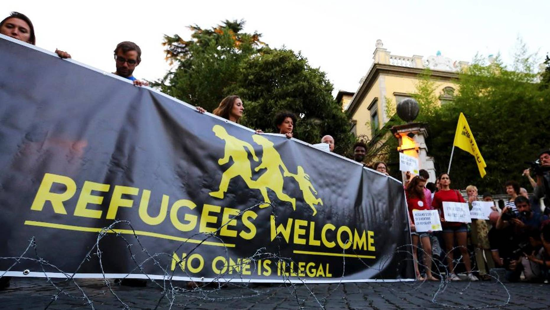 "Activists hold a banner reading ""Refugees Welcome, no one is illegal"" in front of the Hungarian Embassy in Rome, Monday, Sept. 21, 2015, after the Hungarian government warned migrants not to enter the country as it is a crime punishable by imprisonment. Hungarian lawmakers have also approved legislation allowing the government to send troops to help police manage the migration crisis. (Fabio Campana/ANSA via AP) 5 . ANSA / FABIO CAMPANA"