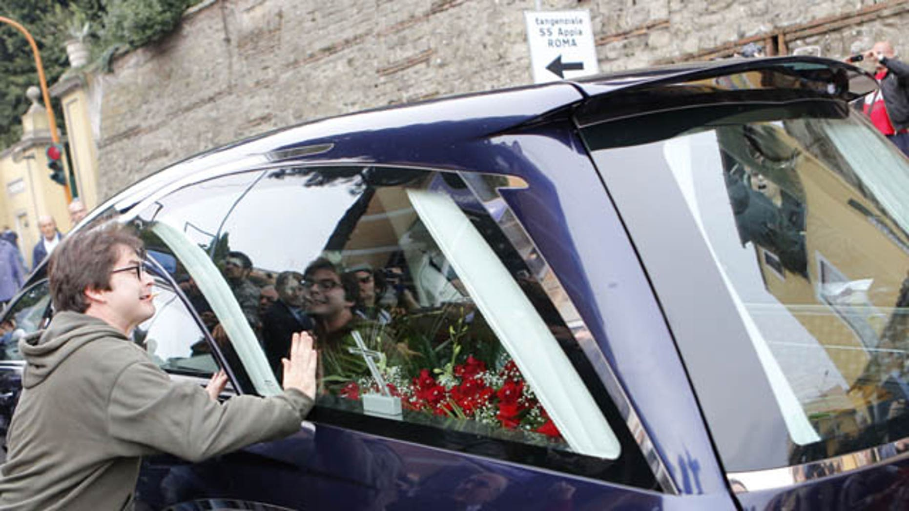 October 15, 2013: A protester bangs his hands on the hearse carrying the coffin of Nazi war criminal Erich Priebke as it arrives at the Society of St. Pius X, a schismatic Catholic group, in Albano Laziale, on the outskirts of Rome Tuesday.