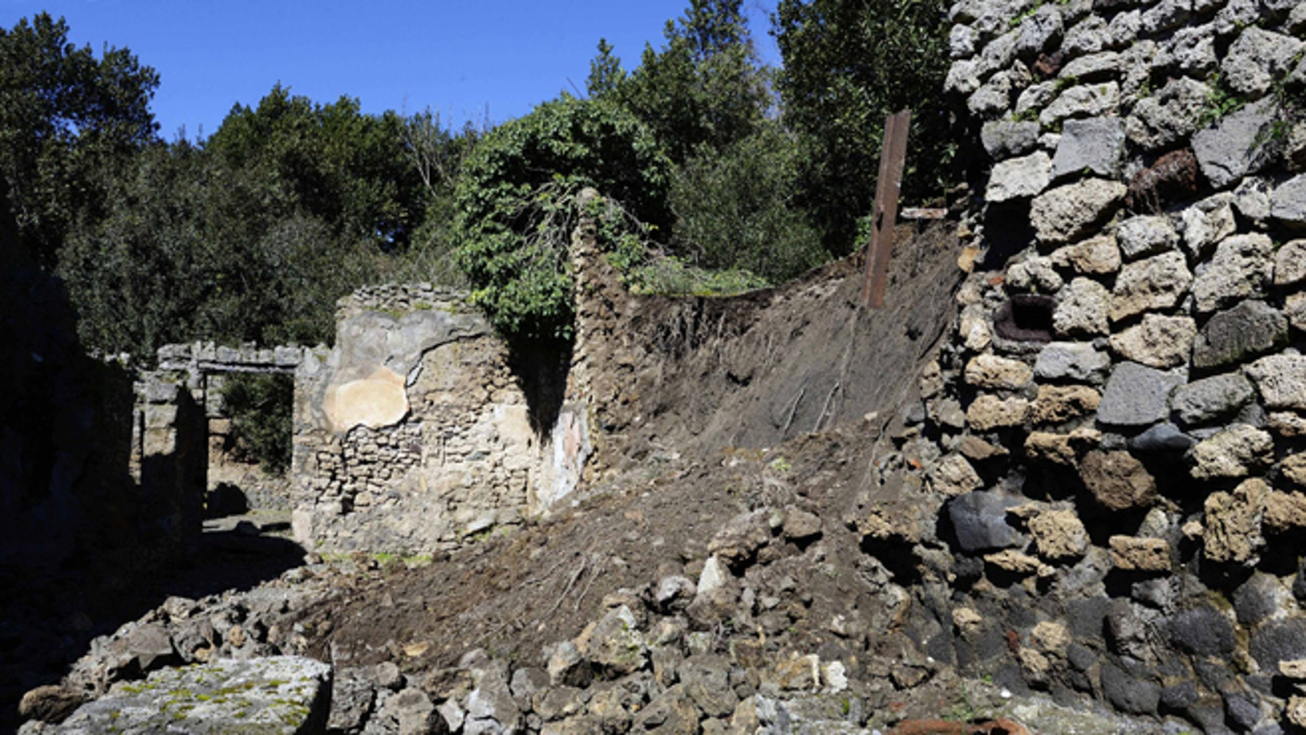 Bricks and rocks are seen on the ground after a section of wall around an ancient shop collapsed in Pompeii as a consequence of a rainstorm, Monday, March 3, 2014.
