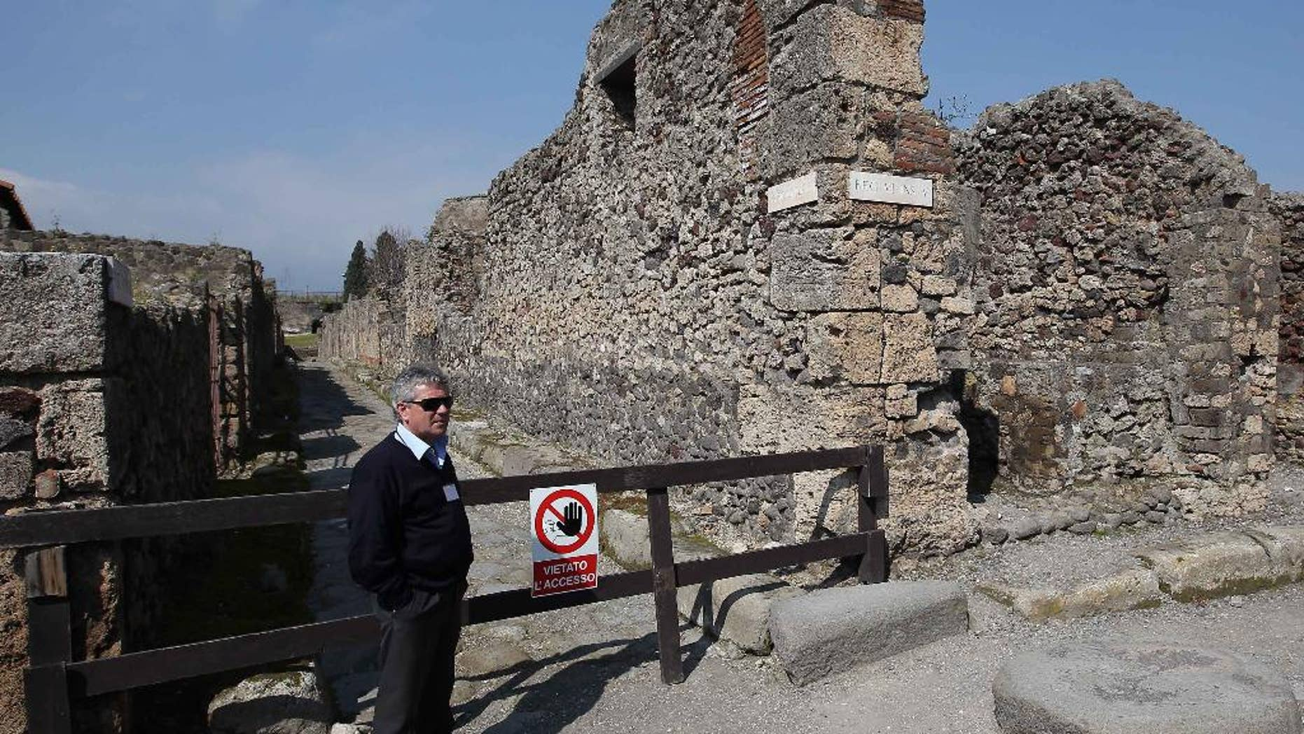 """A man stands by the area where thieves pried off a chunk of an ancient fresco of the Greek goddess Artemis from the walls of Pompeii, Italy, Tuesday, March 18, 2014. Pompeii's archaeological authorities said Tuesday the theft occurred on March 12 in the """"Home of Neptune,"""" in an area of Pompeii's sprawling excavation site not currently open to the public. The thieves used a metal object to scrape off the upper corner of the fresco, making off with a faded, 20-centimeter image of Artemis, the Pompeii authorities said in a statement. It's the latest setback for the popular tourist site, which has seen several walls collapse in recent months due to heavy rains. Similar collapses in recent years have prompted an infusion of EU funds. (AP Photo/Marco Cantile, Lapresse)"""