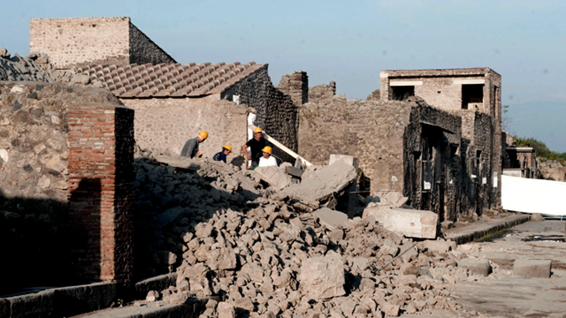 Workers stand among debris in the ancient Roman city of Pompeii, Italy, Saturday, Nov. 6, 2010. Officials say that a house in the ancient Roman city of Pompeii once used by gladiators to train before combat has collapsed. The site was closed at the time and nobody was injured. The office of Pompeii's archaeological superintendent said the collapse occurred Saturday at around 6 a.m. (0500 GMT). Attendants opening the site saw the collapse about an hour later.