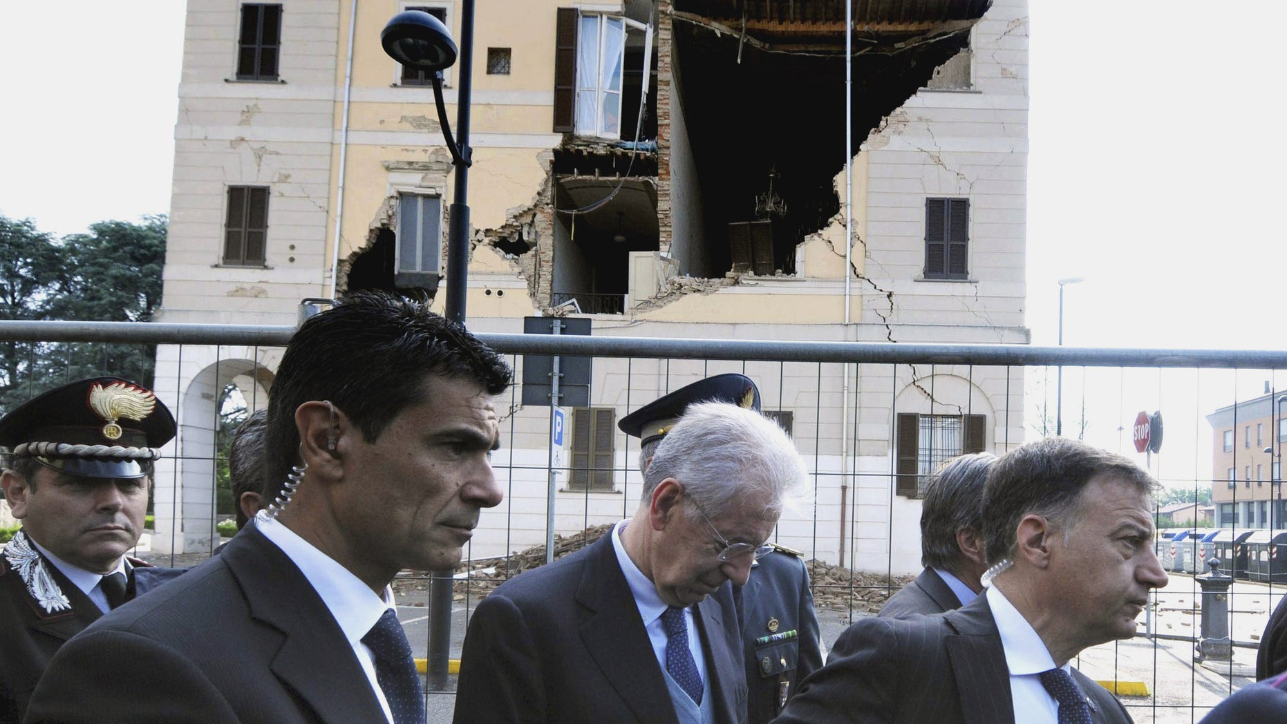 May 22, 2012: Italian Premier Mario Monti, center, looks down as he walks past the damaged town hall of Sant'Agostino, during a visit to the area hit by a quake.