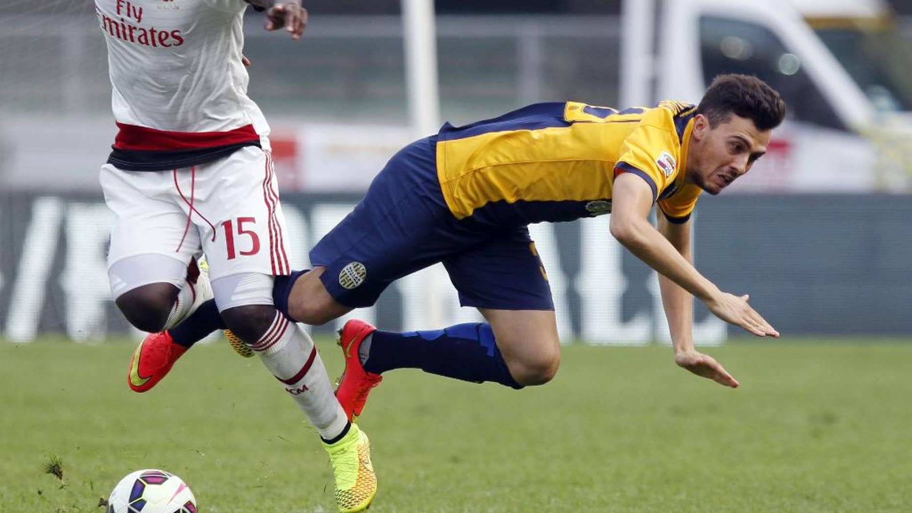 AC Milan's Michael Essien, left, fights for the ball with Hellas Verona's Gustavo Campanharo during a Serie A soccer match at the Bentegodi stadium in Verona, Italy, Sunday, Oct. 19, 2014. (AP Photo/Felice Calabro')