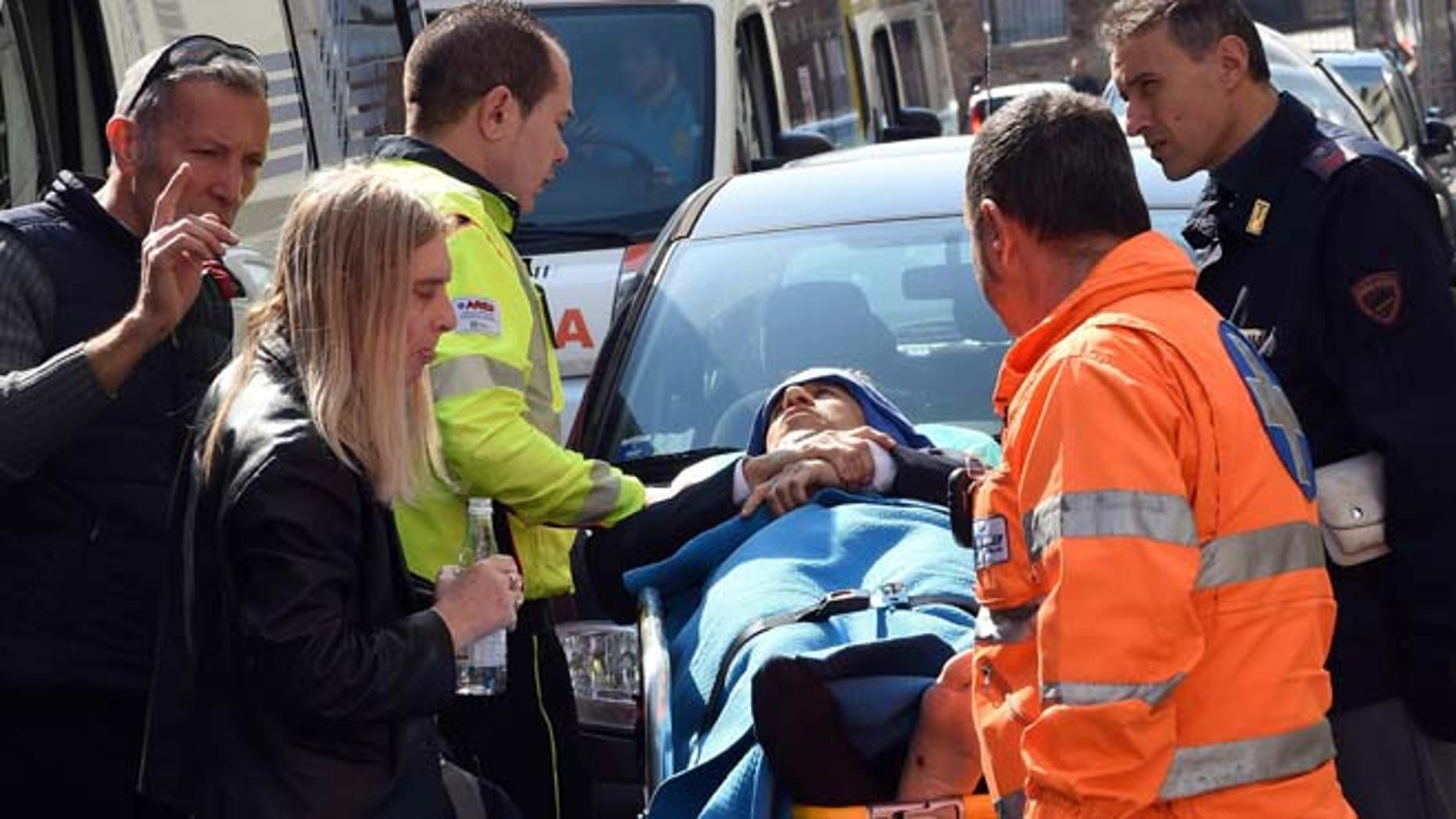 April 9, 2015: Rescuers and police help an injured man outside the tribunal building in Milan, Italy, after a shooting erupted inside a courtroom.