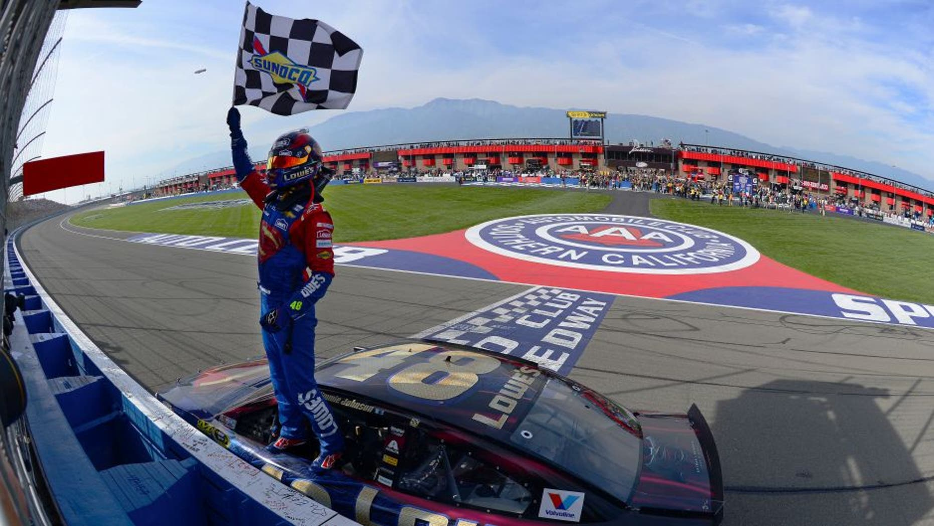 FONTANA, CA - MARCH 20: Jimmie Johnson, driver of the #48 Lowe's / Superman Chevrolet, celebrates after taking the checkered flag during the NASCAR Sprint Cup Series Auto Club 400 at Auto Club Speedway on March 20, 2016 in Fontana, California. (Photo by Robert Laberge/Getty Images)