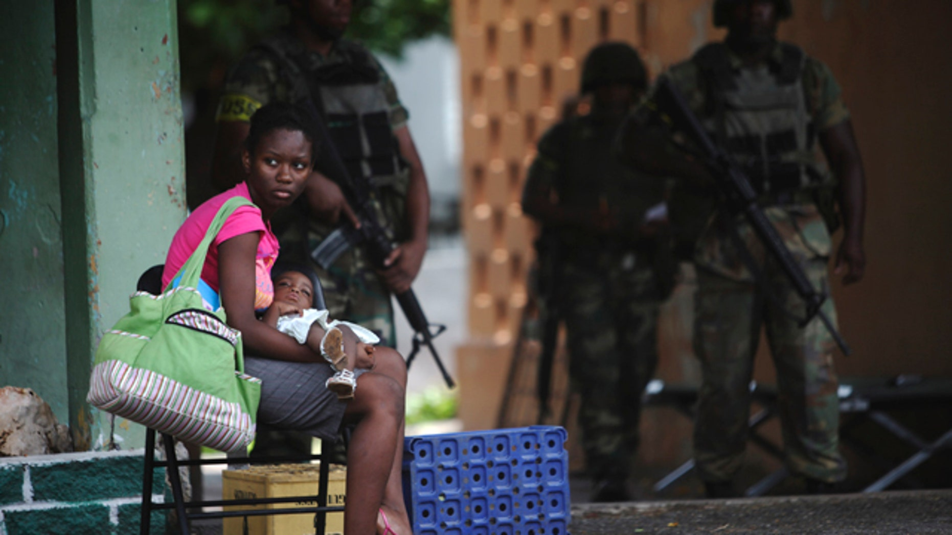 May 27: A woman sits with her daughter as soldiers stand guard in the Tivoli Gardens neighborhood of Kingston, Jamaica.