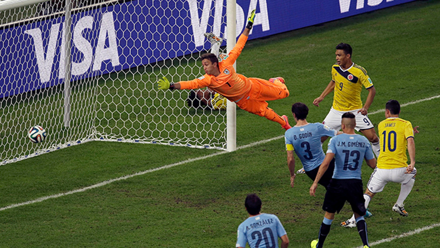 Colombia's James Rodriguez, right, scores his side's second goal past Uruguay's goalkeeper Fernando Muslera during the World Cup round of 16 soccer match between Colombia and Uruguay at the Maracana Stadium in Rio de Janeiro, Brazil, Saturday, June 28, 2014. (AP Photo/Themba Hadebe)