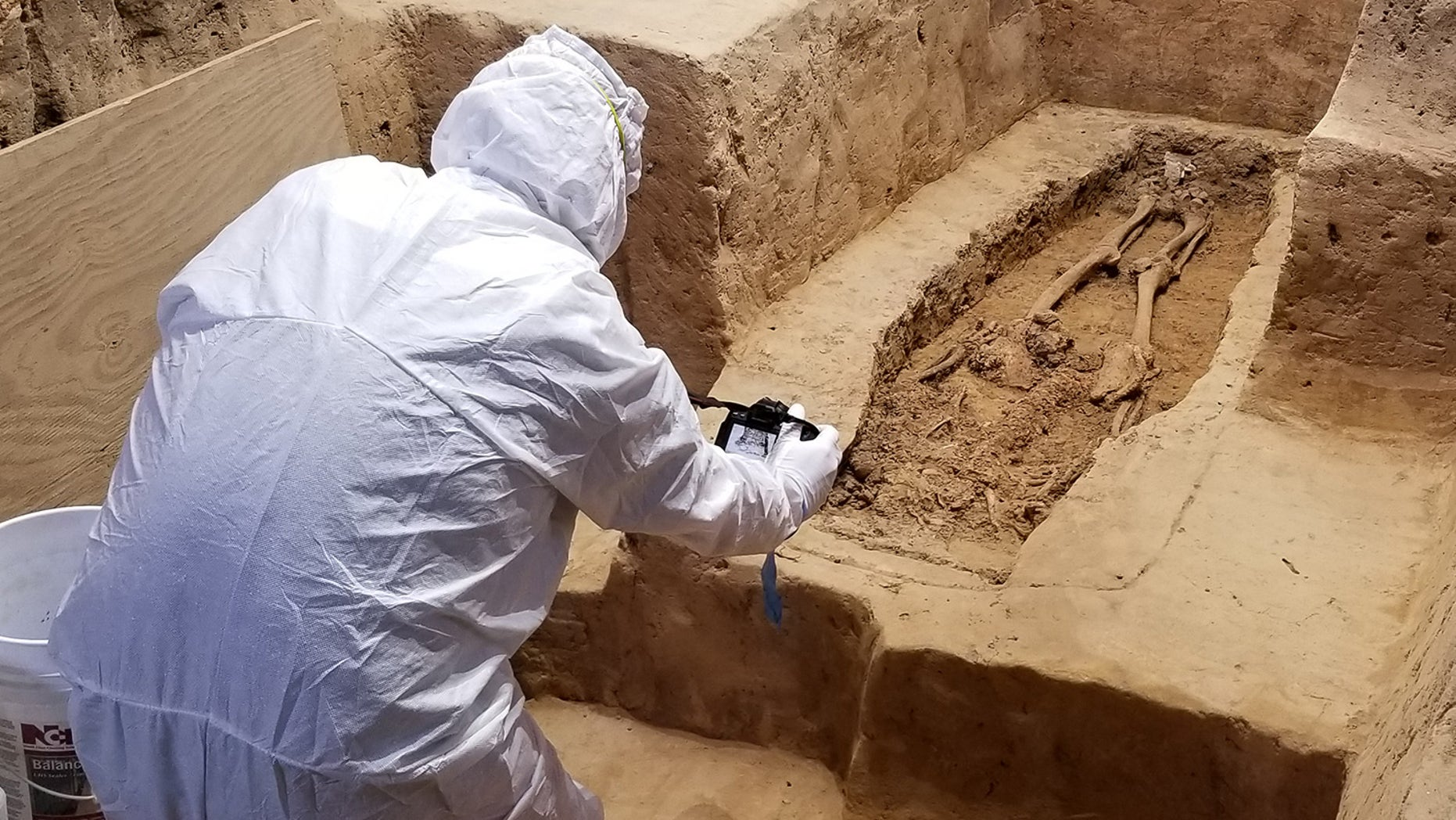 An archaeologist investigates the burial while wearing a suit that will minimize contamination to the historical site.