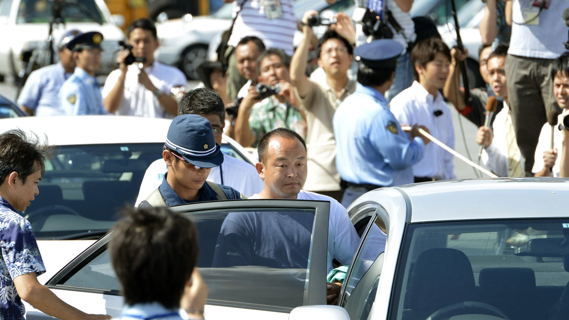 Aug. 16, 2012: An activist, center, is transferred after being arrested for landing on a set of islets known as Senkaku in Japanese and Diaoyu in Chinese, at a port in Naha, Okinawa prefecture, southern Japan.