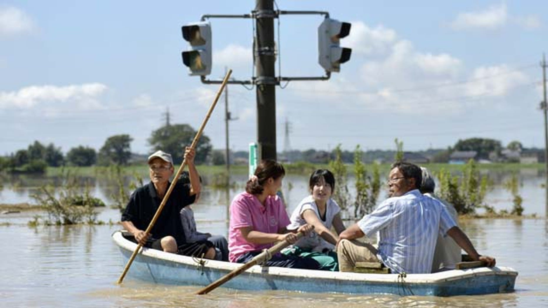 Sept. 11, 2015: Residents paddle a boat past a traffic light in the flooded road in Joso, Ibaraki prefecture, northeast of Tokyo. (Kyodo News via AP)