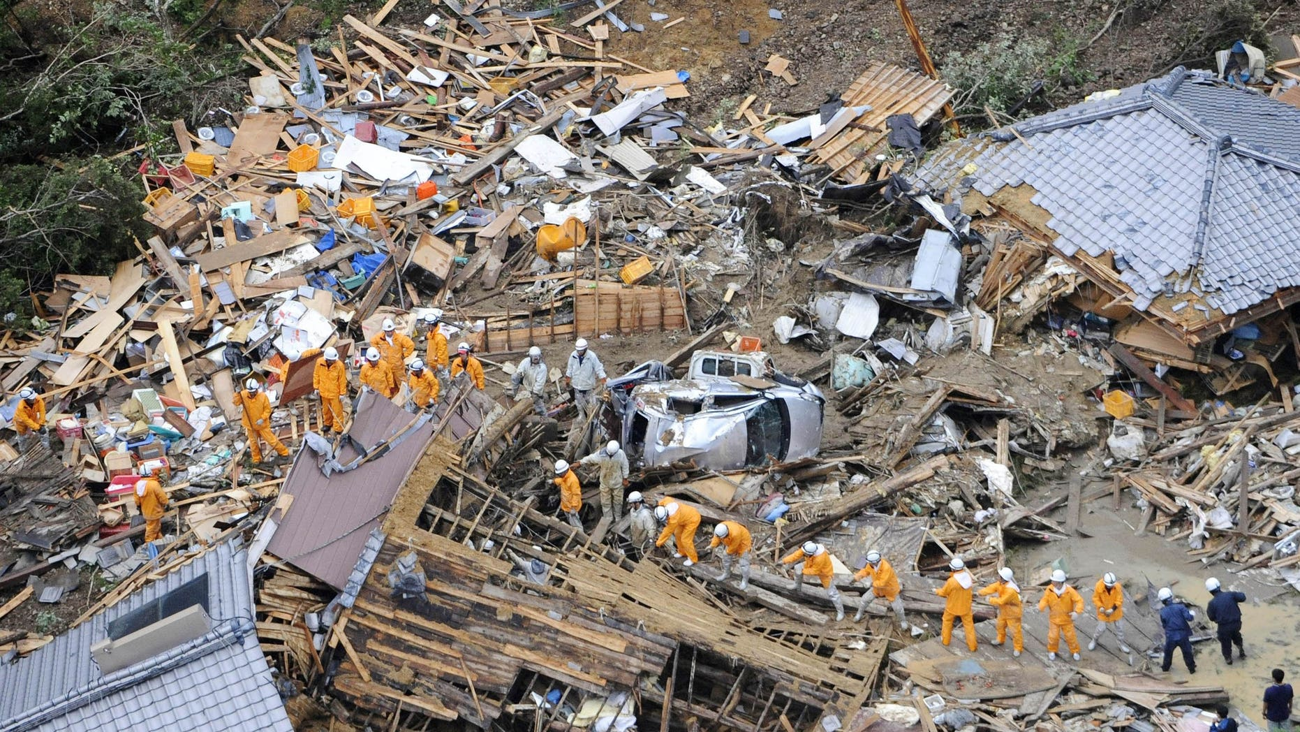 September 4: Volunteer firefighters search destroyed houses for missing people after heavy downpours by Typhoon Talas caused a landslide at Tanabe, central Japan. The storm dumped record amounts of rain Sunday in western and central Japan as it turned towns into lakes, washed away cars and triggered mudslides that obliterated houses.