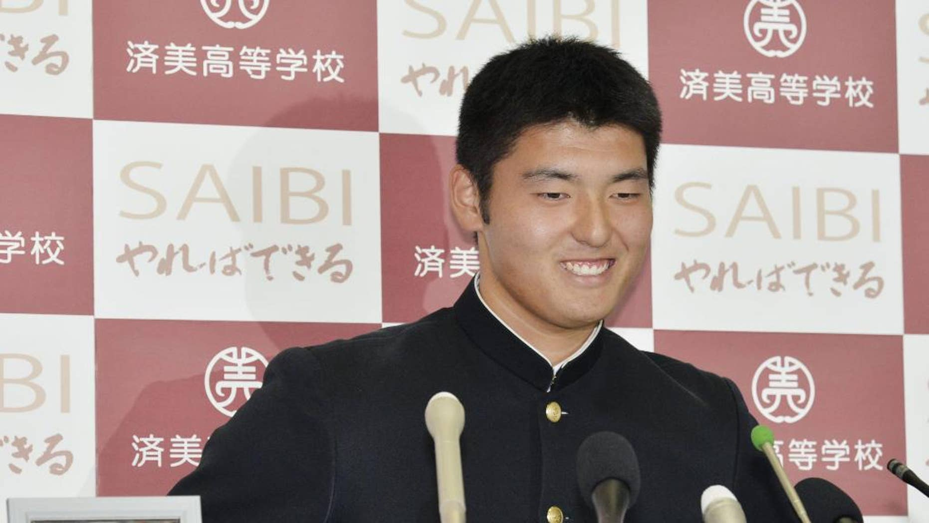 Japan's high school pitching star Tomohiro Anraku smiles next to a photo of his baseball team head coach Masanori Joko who died in September during a news conference at Saibi High School in Matsuyama, western Japan, Thursday, Oct. 23, 2014, after he was chosen first overall in Nippon Professional Baseball's amateur draft and was headed to the former team of New York Yankees pitcher Masahiro Tanaka. The Yakult Swallows and Rakuten Eagles selected Anraku, whose fastball has been clocked as high as 97 mph (156 kph), with the first and second picks respectively, and the Eagles won a lottery for the highly touted 17-year-old right-hander. (AP Photo/Kyodo News) JAPAN OUT, CREDIT MANDATORY