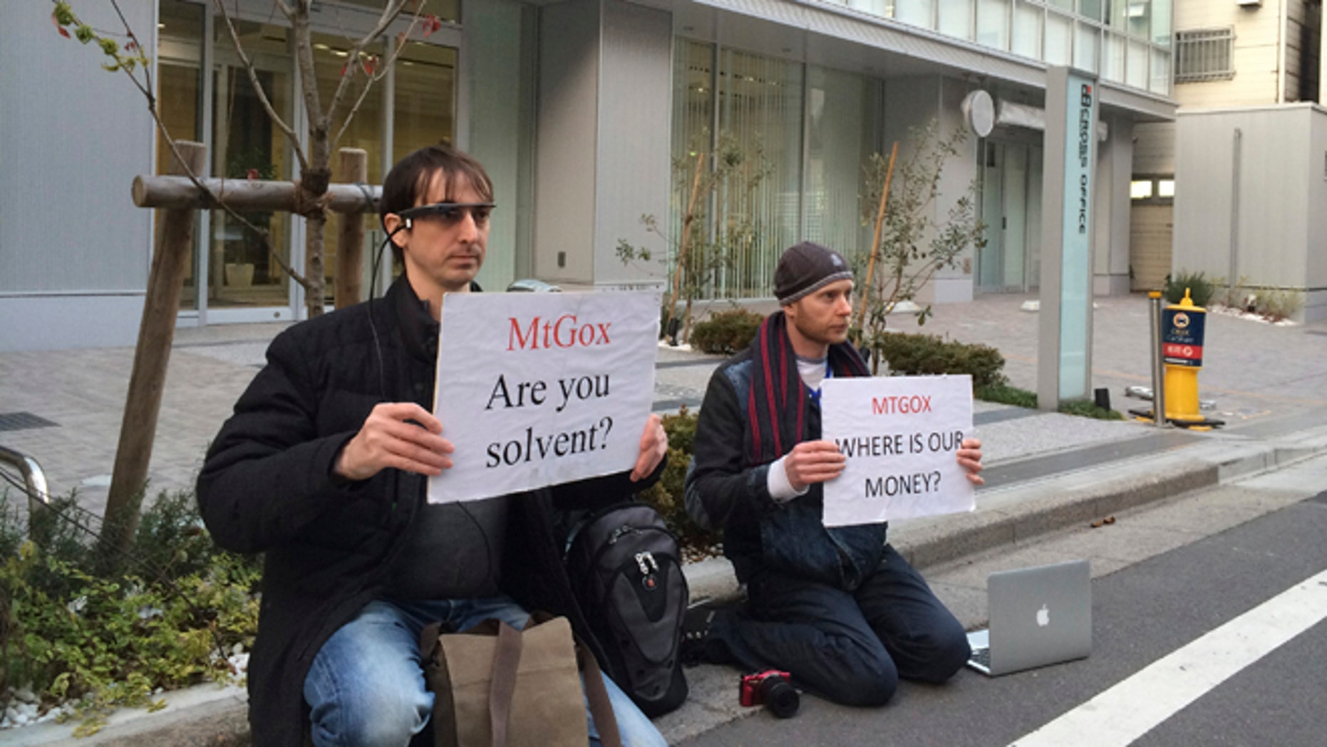 Feb. 25, 2014: Bitcoin trader Kolin Burges, right, of London and American Aaron (only his first name was given) hold protest signs as they conduct a sit-in in front of the office tower housing Mt. Gox in Tokyo Tuesday.