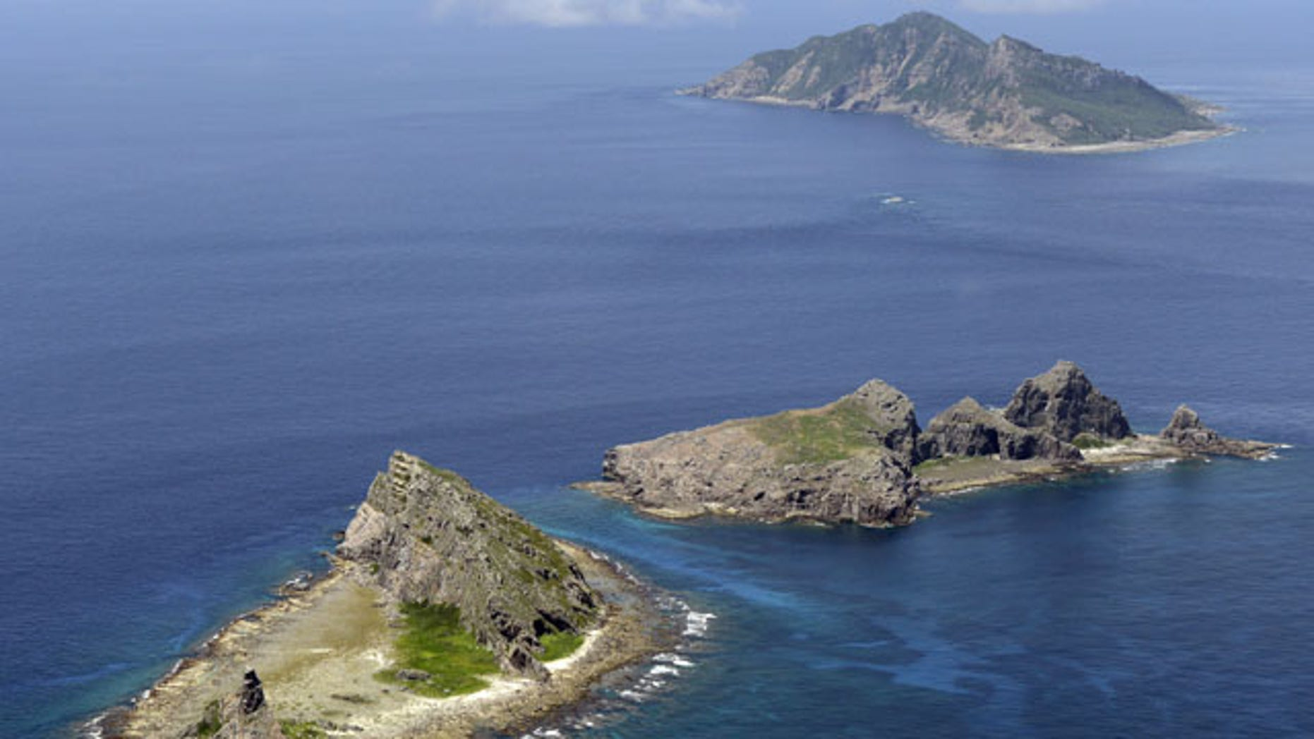 In this Sept. 2012 photo, the tiny islands in the East China Sea, called Senkaku in Japanese and Diaoyu in Chinese are seen. The Chinese Defense Ministry on Saturday, Nov. 23, 2013, issued a map of an East China Sea Air Defense Identification Zone that includes a chain of disputed islands also claimed by Japan, triggering a protest from Tokyo. (AP Photo/Kyodo News)