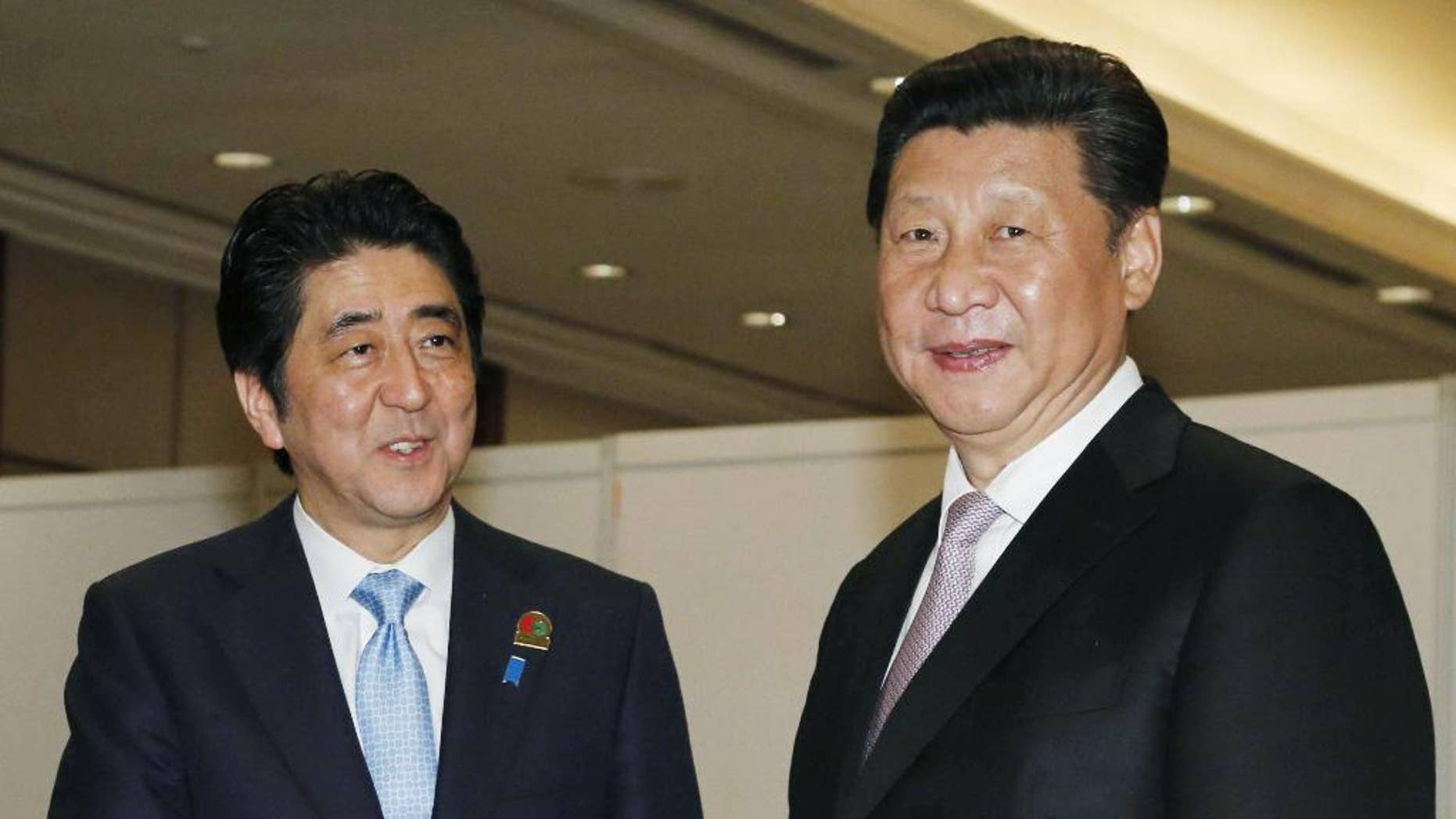 FILE - In this April 22, 2015 file photo, Chinese President Xi Jinping, right, shakes hands with Japan's Prime Minister Shinzo Abe during their bilateral meeting on the sideline of the Asian African Summit in Jakarta, Indonesia. Abe will not attend a military parade in China next week to commemorate the end of World War II, the government's top spokesman said Monday, Aug. 24, 2015. (Kyodo News via AP, File) JAPAN OUT, MANDATORY CREDIT