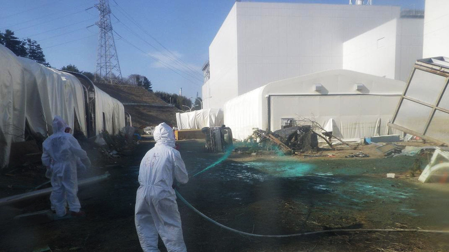 April 1: Workers for the company experimentally spray adhesive synthetic resin over the ground at the Fukushima Dai-ichi nuclear power plant in Okumamachi, northeastern Japan. TEPCO expects the resin spraying to prevent dust exposed to radiation materials from spreading out of the premises. (AP/TEPCO)