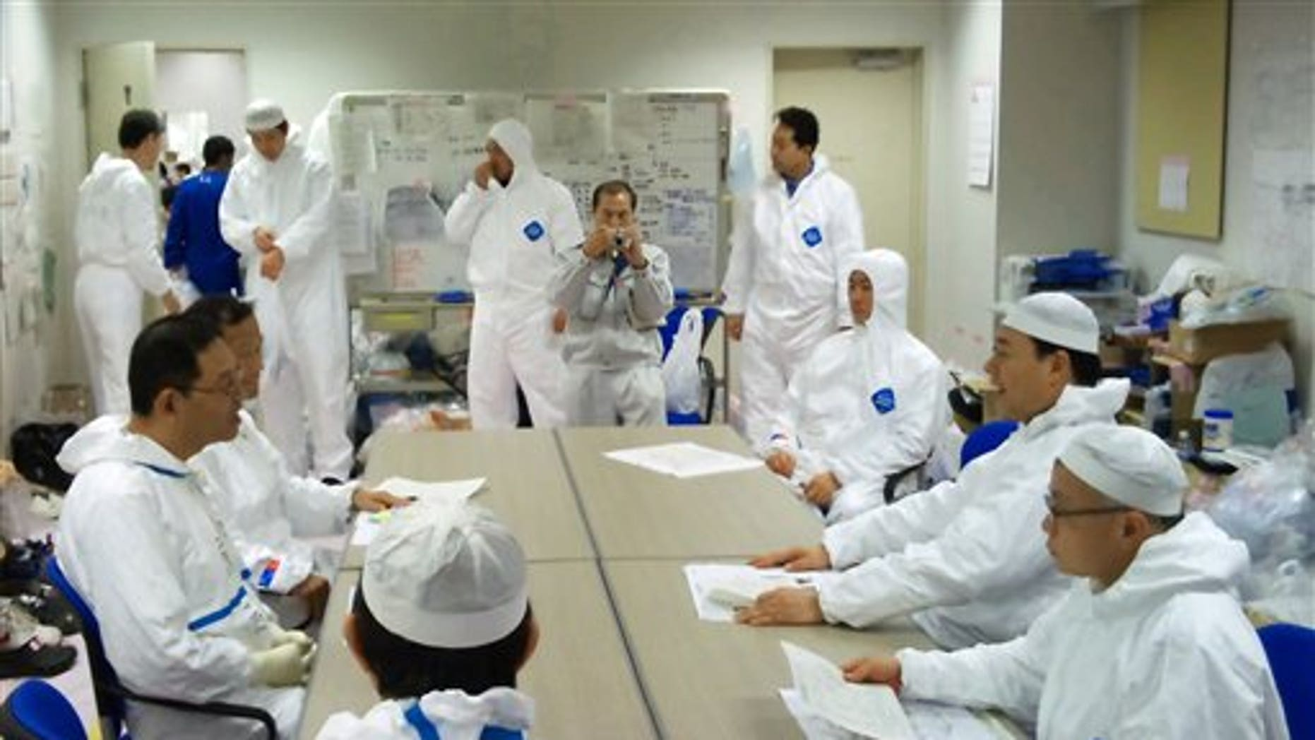 April 9: In this photo released by Nuclear and Industrial Safety Agency via Kyodo News, Japanese Trade Minister Banri Kaieda, second right, in protective suit listens to employees of Tokyo Electric Power Co. inside the waste processing building of the Fukushima Dai-ichi nuclear power plant during his one-day trip to the tsunami-crippled complex in Okuma town, Fukushima Prefecture. (AP/Nuclear and Industrial Safety Agency)