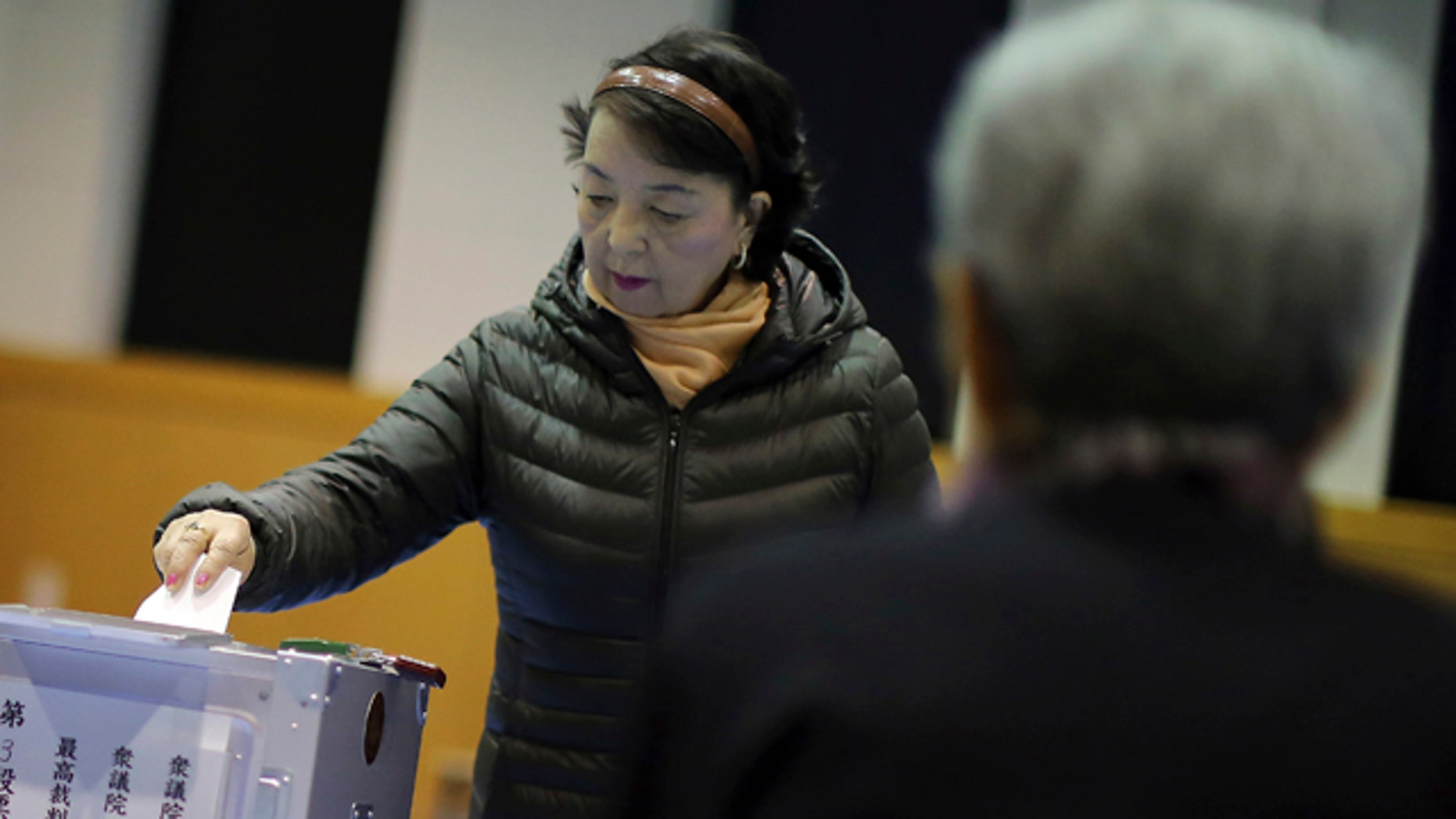 December 14, 2014: A woman casts her vote for parliament's lower house election as a representative, right, of a local election administration commission observes at a polling station in Tokyo. (AP Photo/Eugene Hoshiko)