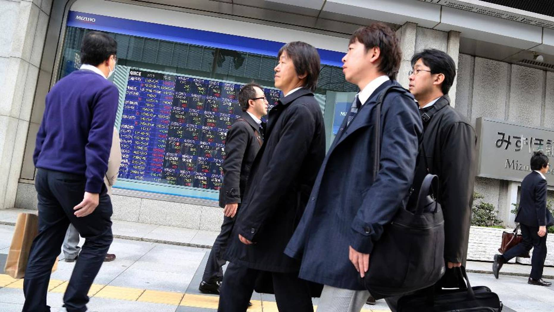 People walk by an electronic stock board of a securities firm in Tokyo, Friday, March 13, 2015. Asian stock markets mostly rose Friday after weak U.S. retail sales alleviated jitters about the Federal Reserve's timetable for raising interest rates. Japan's Nikkei 225 rose 1.4 percent to 19,254.25. (AP Photo/Koji Sasahara)