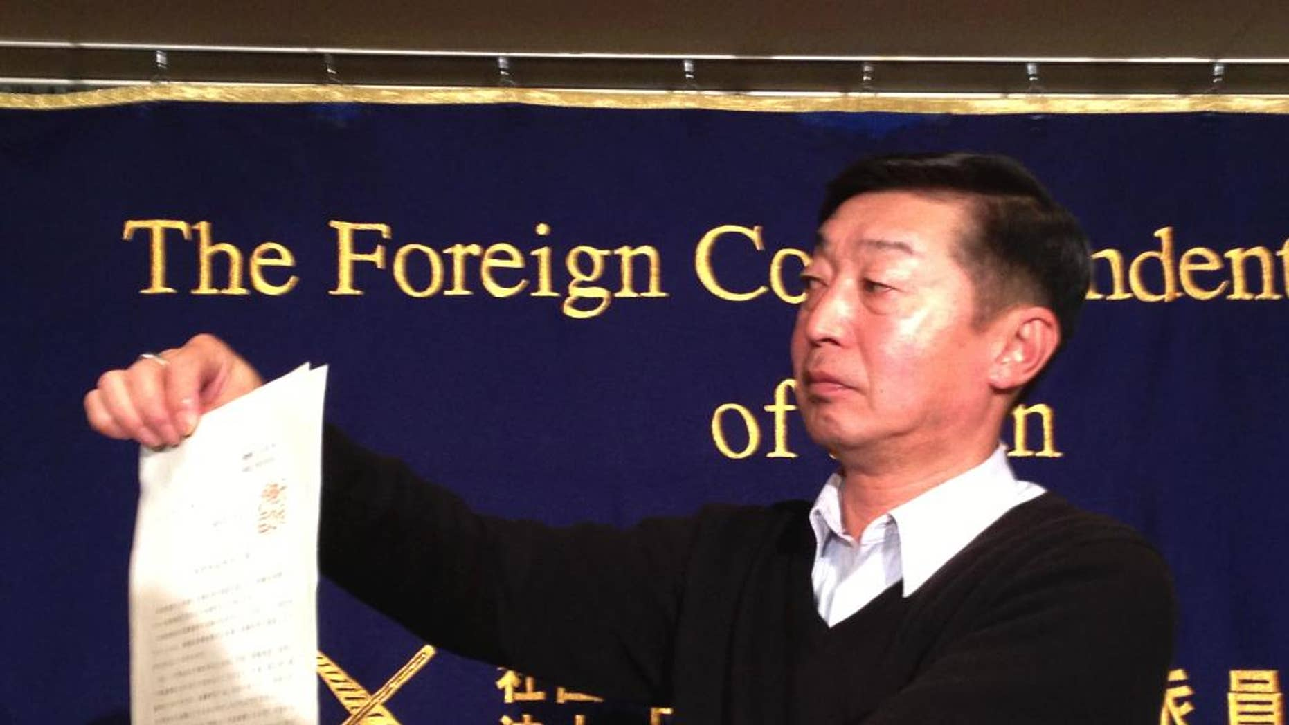 Japanese freelance photographer Yuichi Sugimoto shows the press the original document of an order, signed by Foreign Minister Fumio Kishida, which he was given by Japanese foreign ministry officials at his home, during a news conference in Tokyo Thursday, Feb. 12, 2015. Sugimoto said he was forced to give up his passport because he planned a reporting trip to Syria, which the government has stepped up warnings to its citizens not to visit after two Japanese were killed there in a recent hostage crisis. (AP Photo/Mari Yamaguchi)